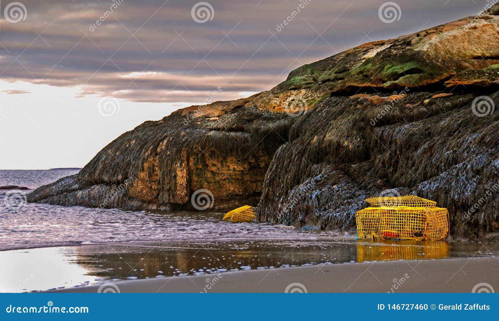 Trampas de la langosta en la playa en Maine con marea y el acantilado rocoso