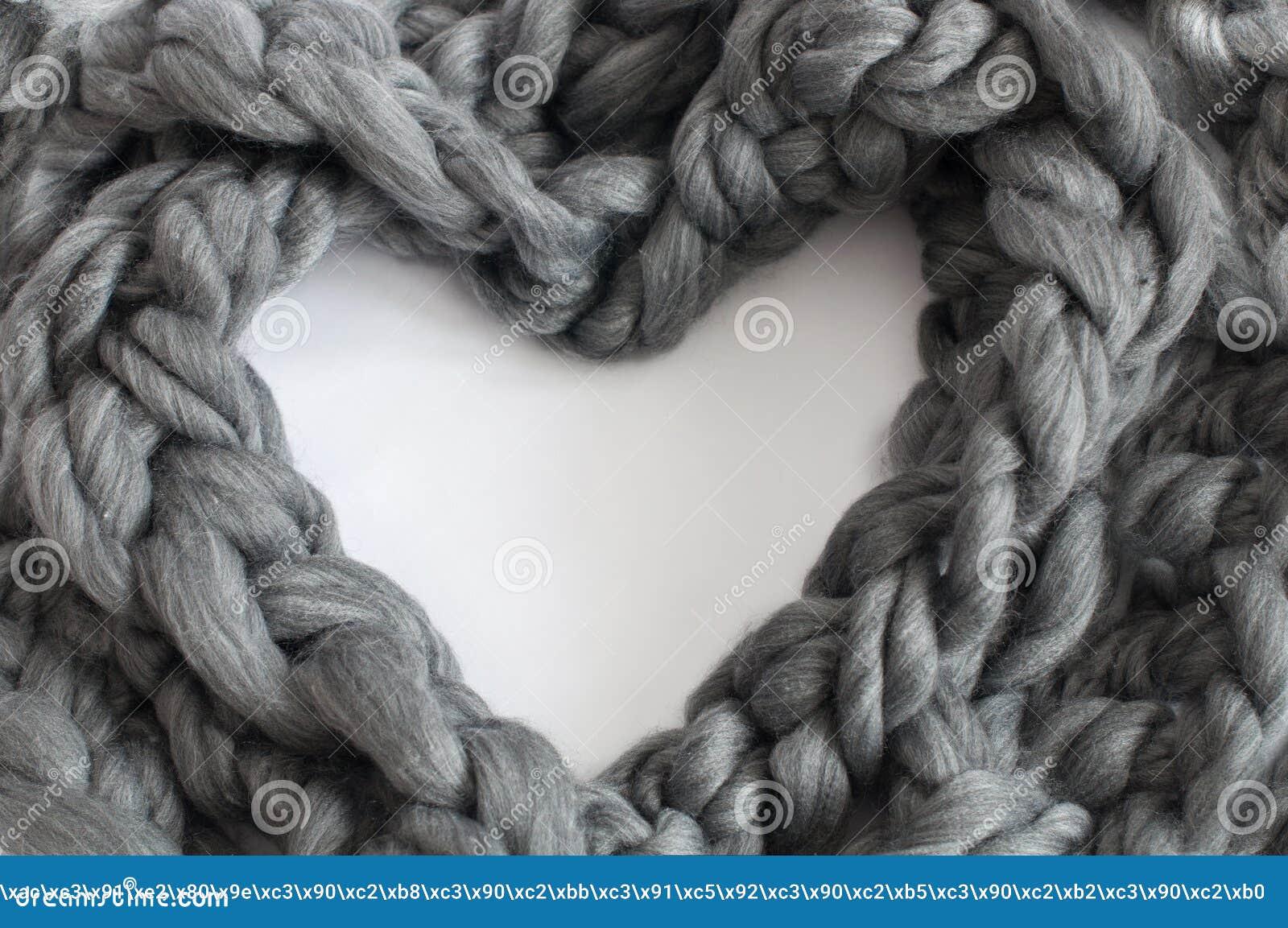Trança de lã cinzenta em uma forma do coração