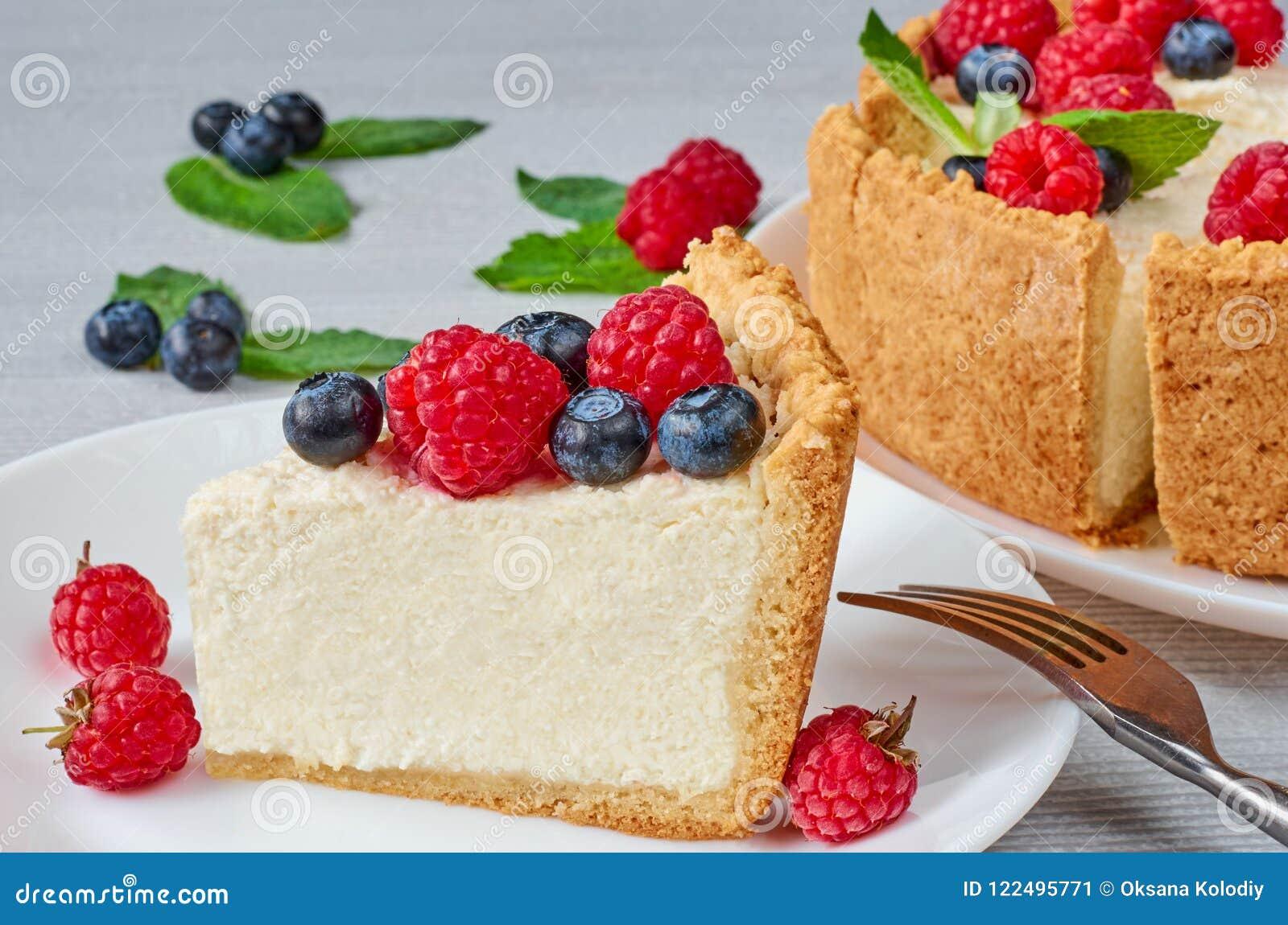 Tranche de gâteau au fromage classique avec les baies fraîches du plat blanc - dessert organique sain d été Gâteau au fromage ave