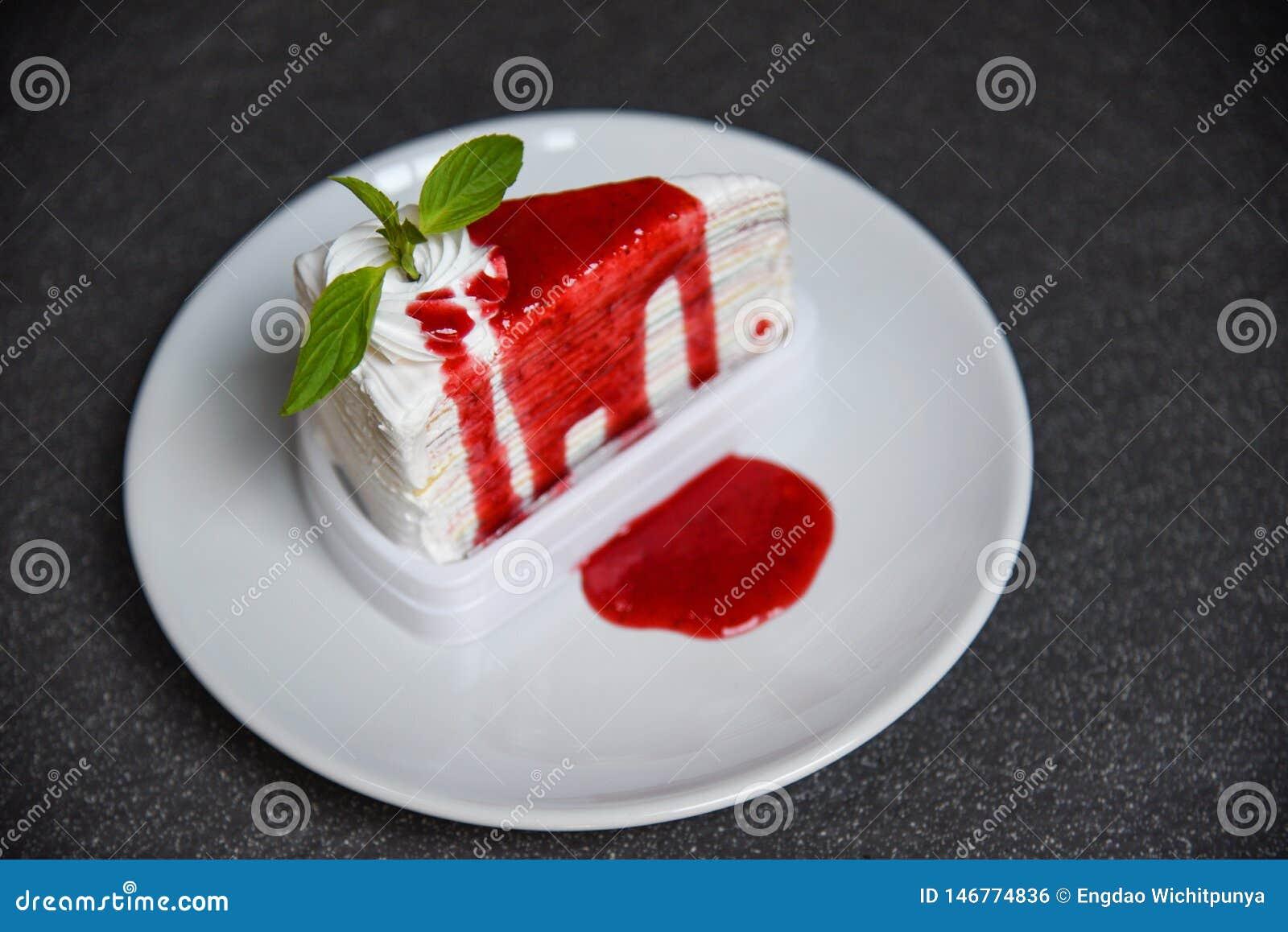 Tranche de gâteau de crêpe avec de la sauce à fraise du plat blanc sur le fond foncé