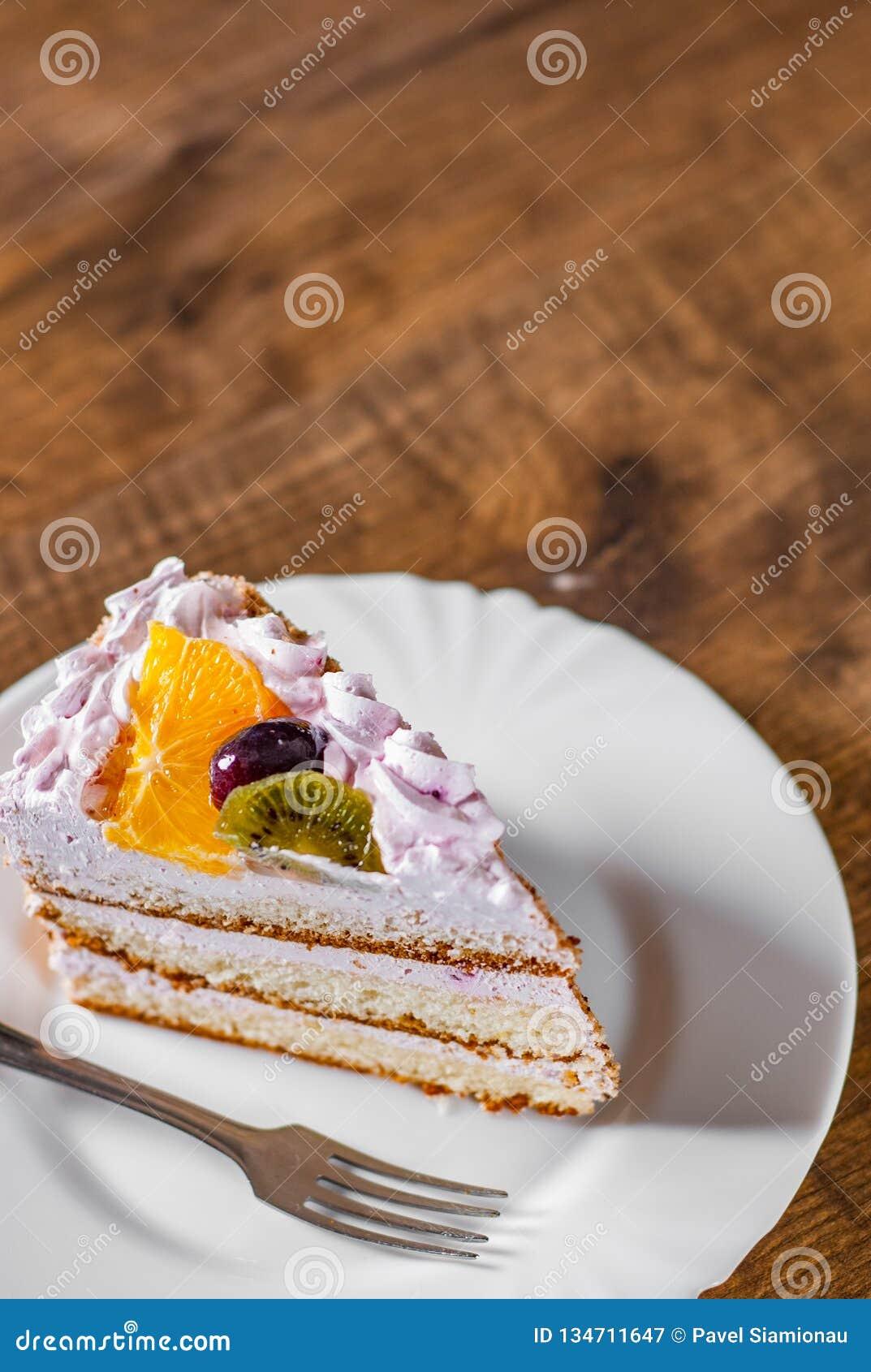 Tranche de gâteau d anniversaire posé avec de la crème avec le fruit dans un plat sur en bois