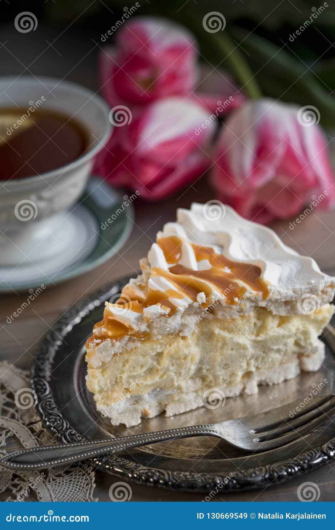 Tranche de gâteau de meringue et d une tasse de thé et de tulipes
