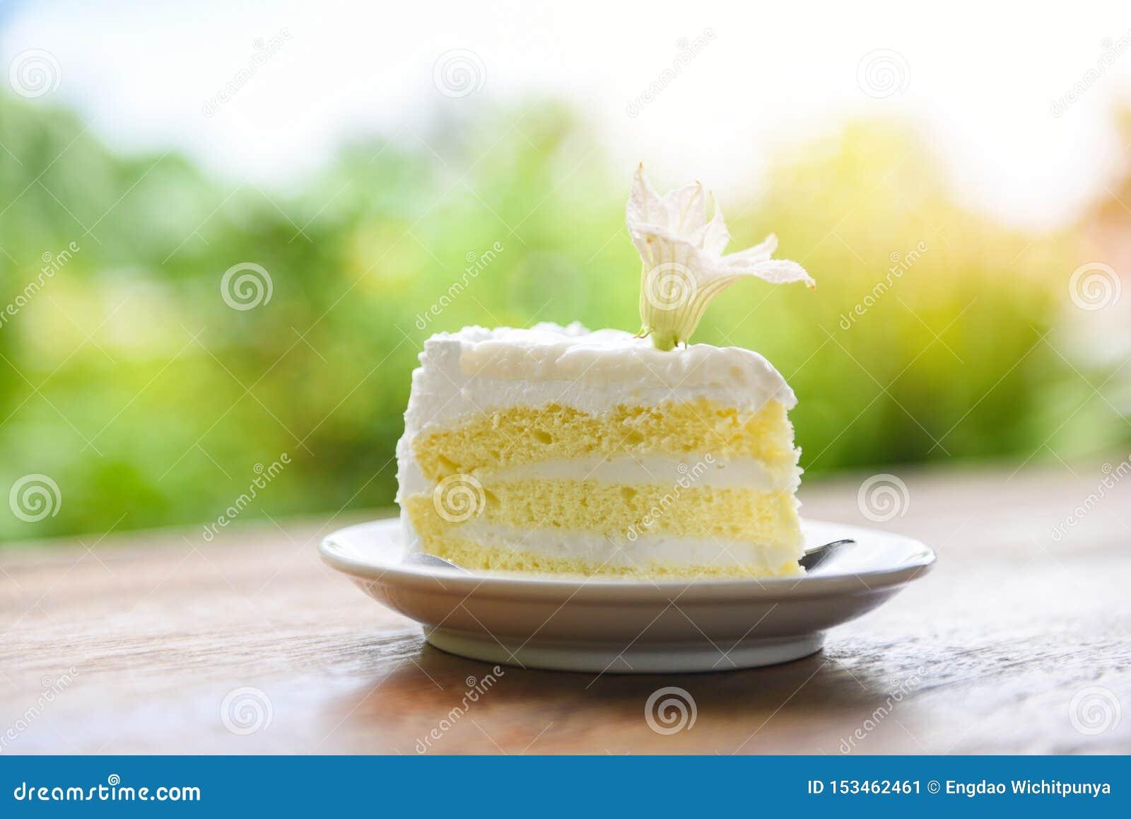 Tranche de gâteau sur le palte blanc avec la fleur sur le fond en bois de nature de table - gâteau de noix de coco délicieux