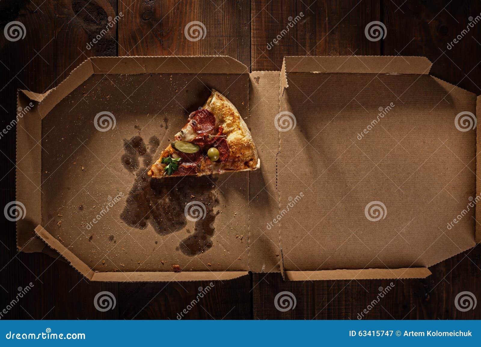 Tranche de pizza dans dans la boîte de la livraison sur le bois