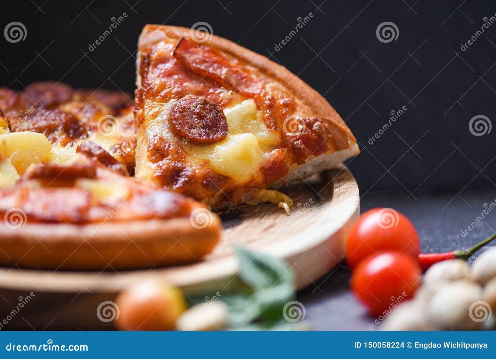 Tranche de pizza sur la feuille en bois de basilic de piments de plateau et de tomate sur fromage traditionnel italien savoureux
