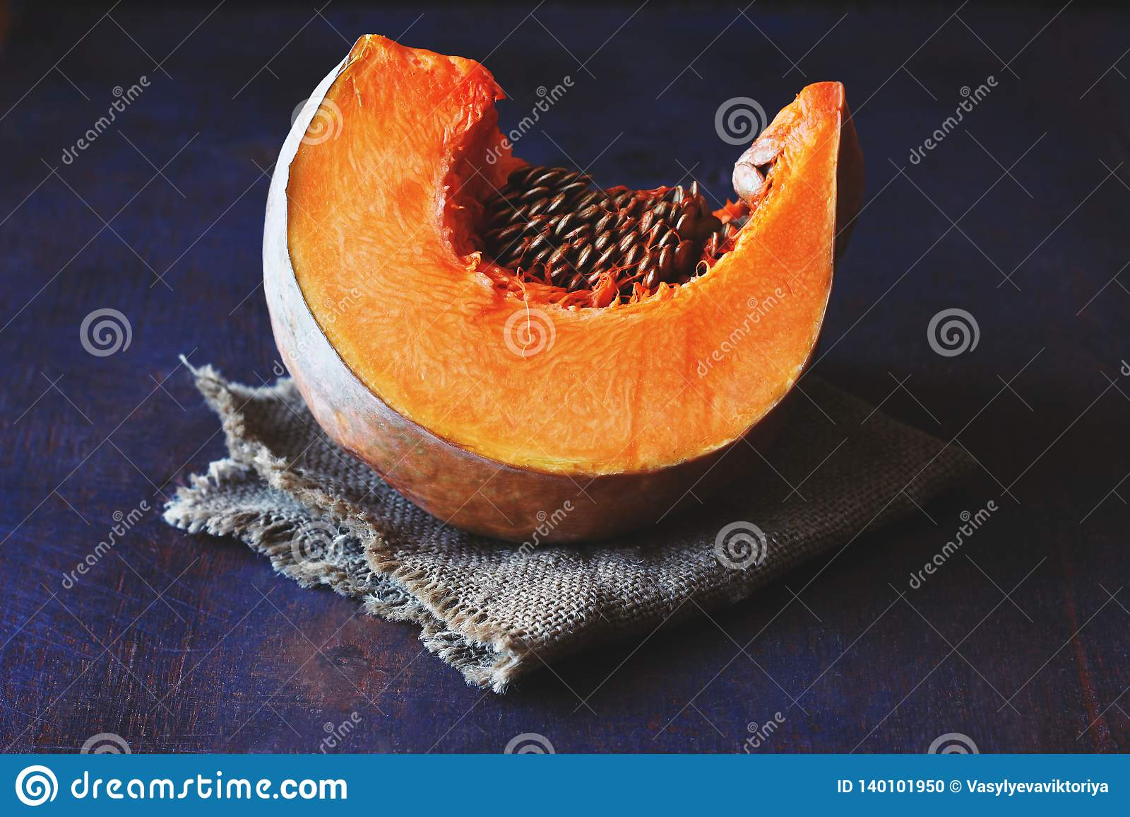Tranche orange lumineuse de potiron avec des graines sur une serviette