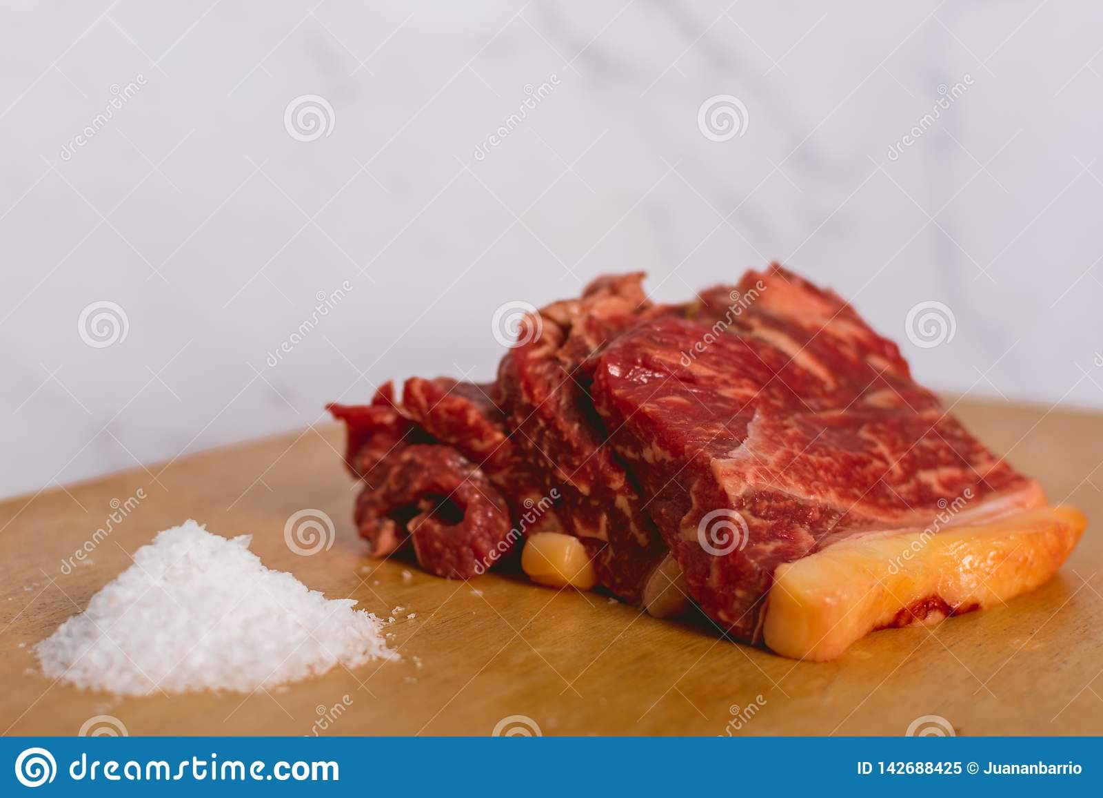 Tranches crues fraîches de bifteck de viande de boeuf sur le conseil coupé en bois au-dessus du fond blanc
