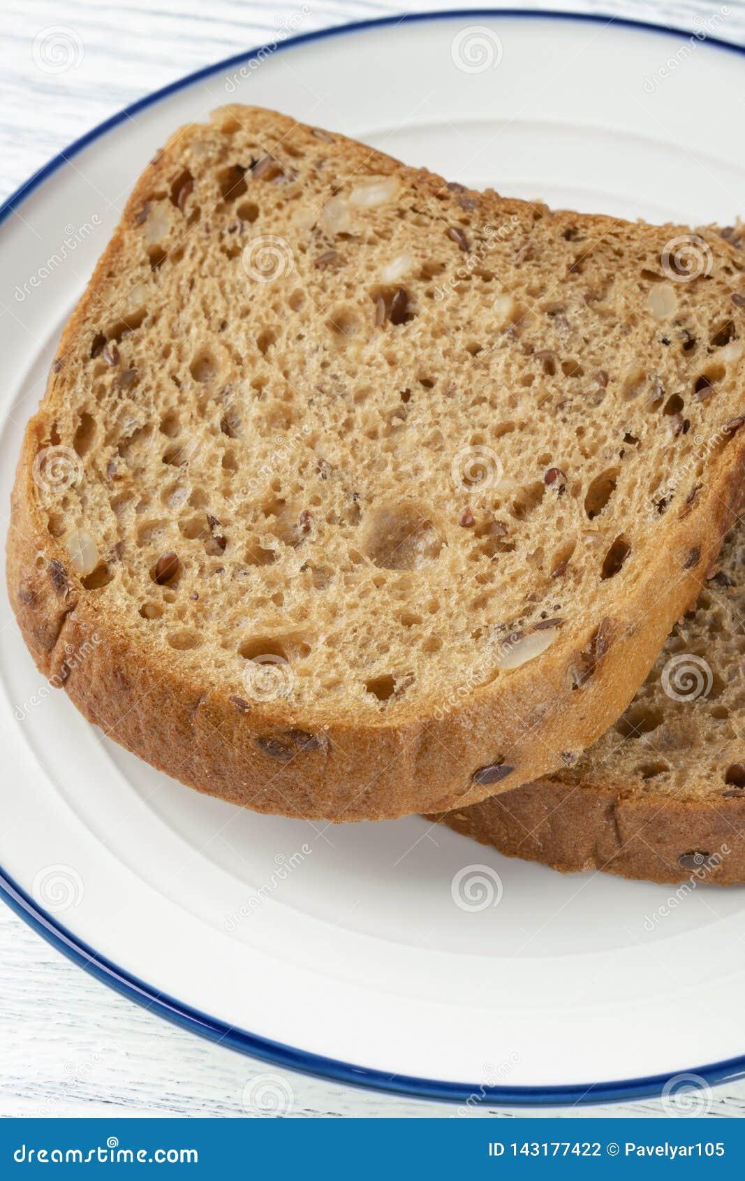 Tranches de pain de grain avec le moule D un plat blanc avec une rayure bleue Sur une table en bois
