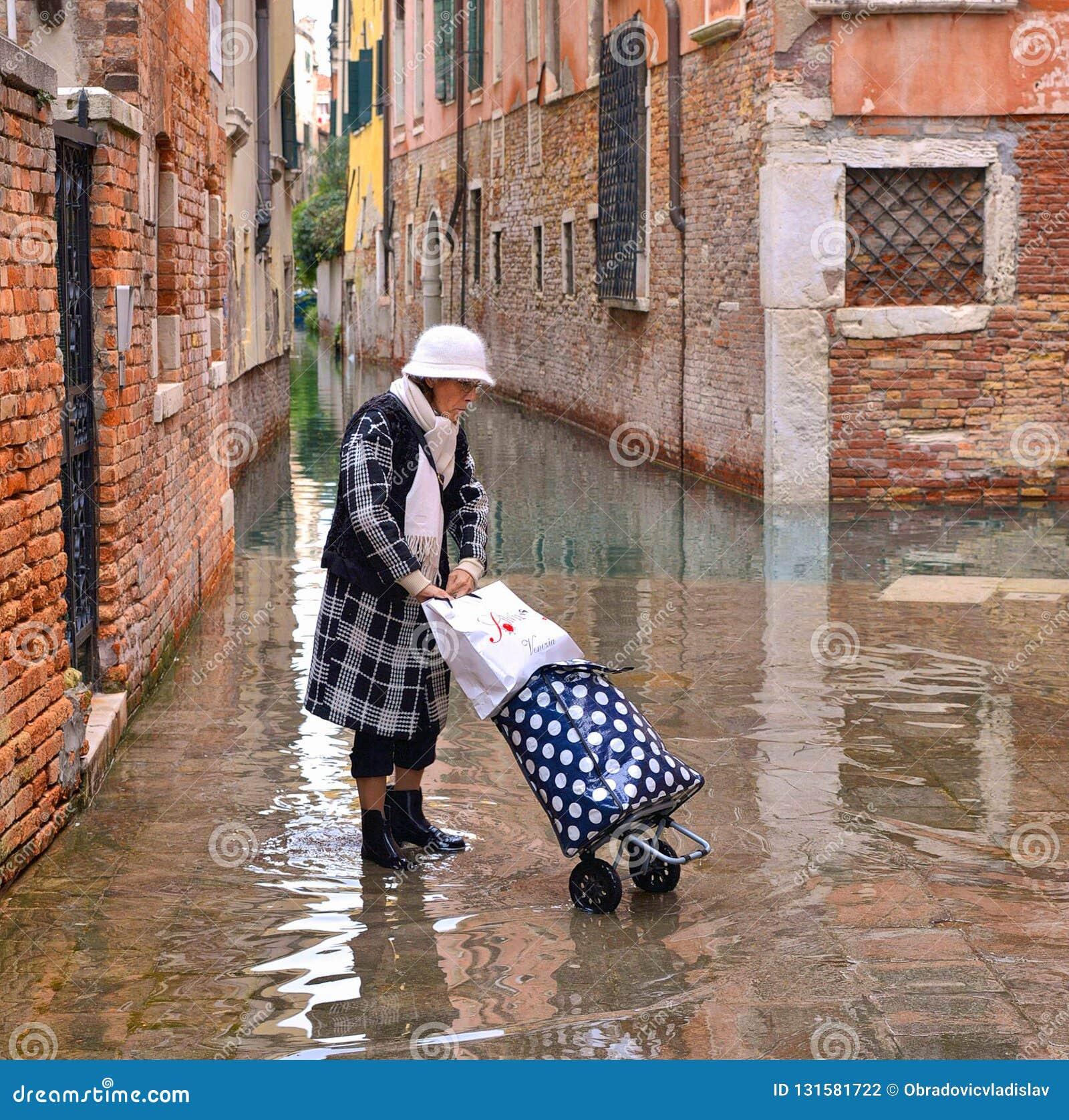 Trandy modna dojrzała kobieta z getrami, butami i walizką przy przypływem w starym przesmyku, zalewał ulicę