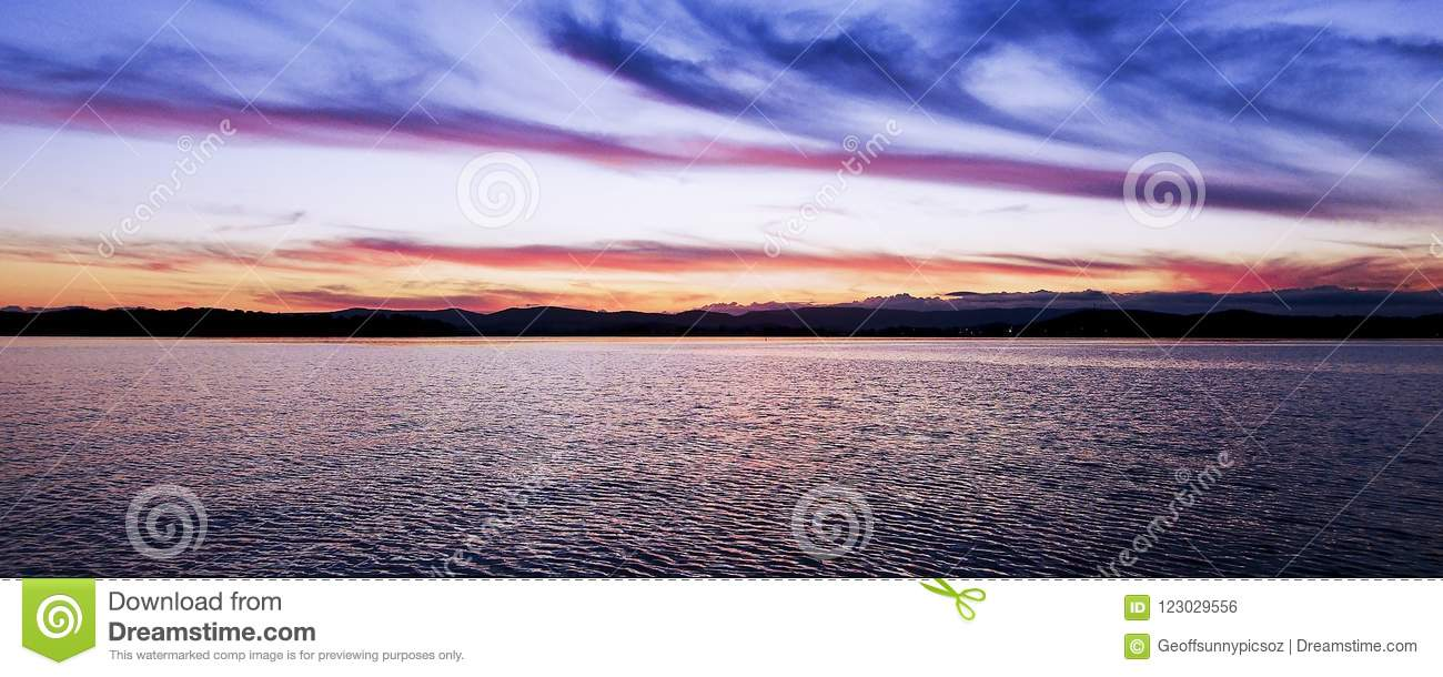 Tranquill peaceful red coloured cirrus cloud, sunset seascape.