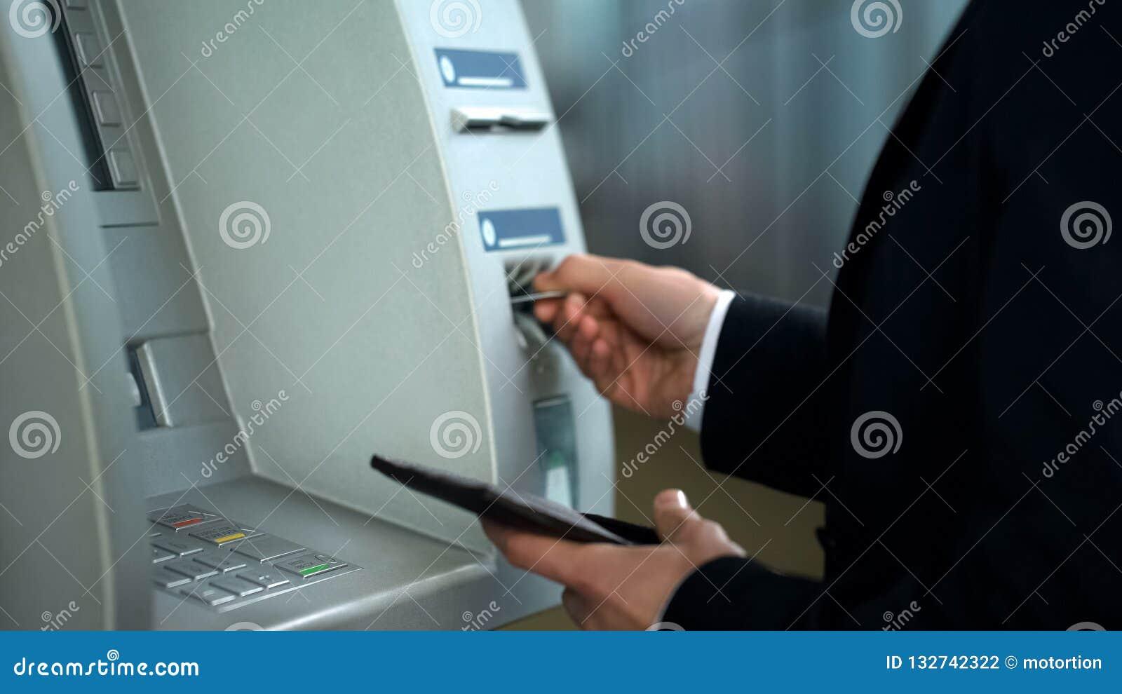Transação de operação bancária de terminação do homem de negócios, removendo o cartão do ATM, operação bancária
