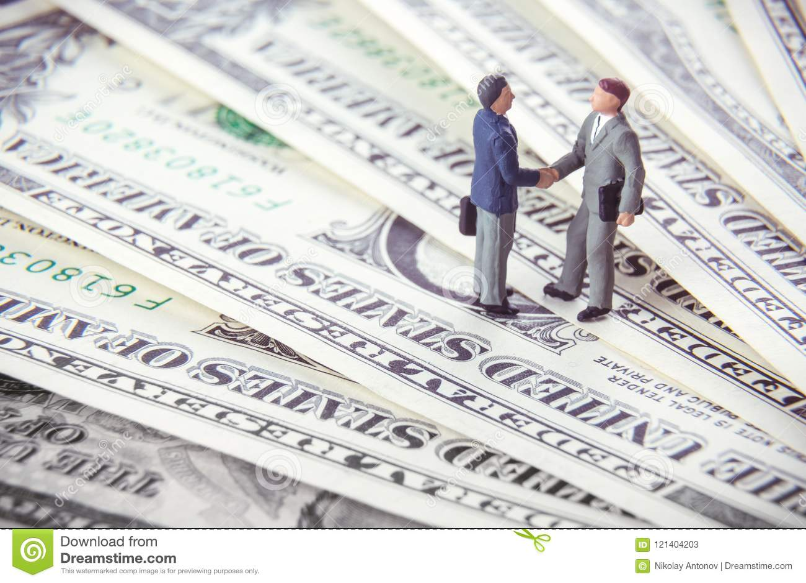 Transactie of overeenkomsten en succesconcept Twee miniatuurzakenlieden die handen schudden terwijl status op de Amerikaanse bede