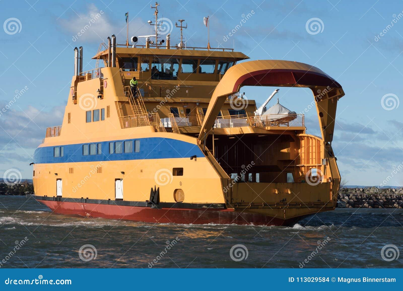 Transbordador amarillo grande del vehículo que llega al puerto