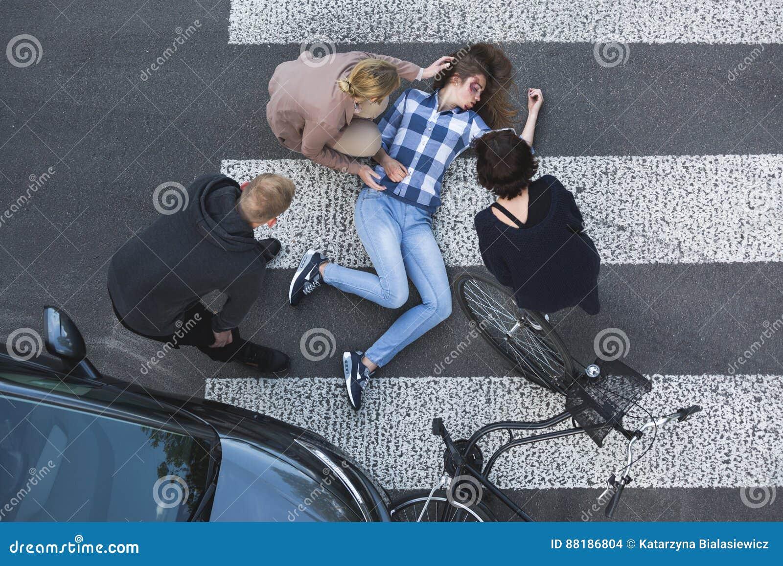 Transeuntes que ajudam a víctima de um acidente de trânsito