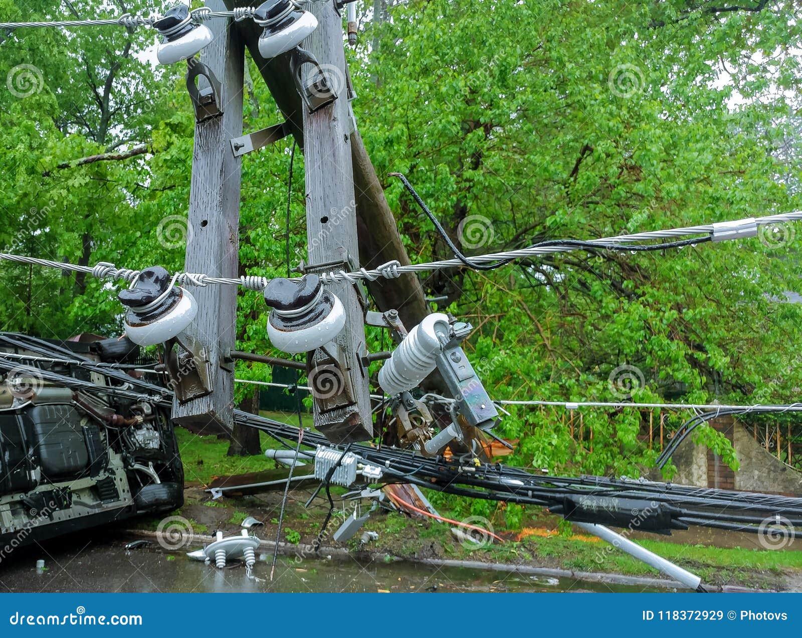 Transformator auf einem Pfosten und einem Baum, die über Stromleitungen über einer Straße nach Hurrikan legen, bewegte sich herüb