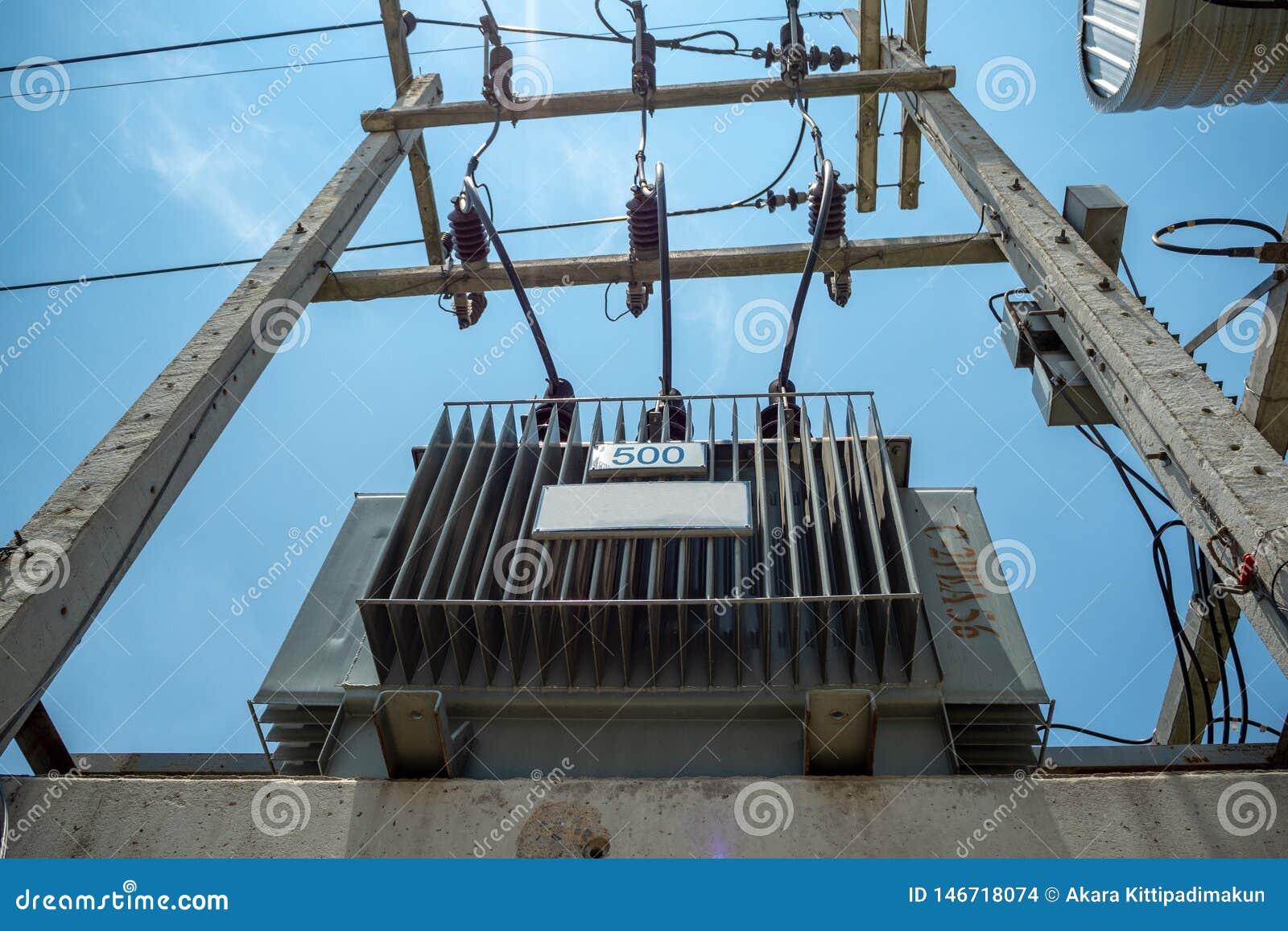 Transformatorn för elektrisk fördelning med höga spänningskablar och skyddsutrustning installerar på konkret pol med blå himmel
