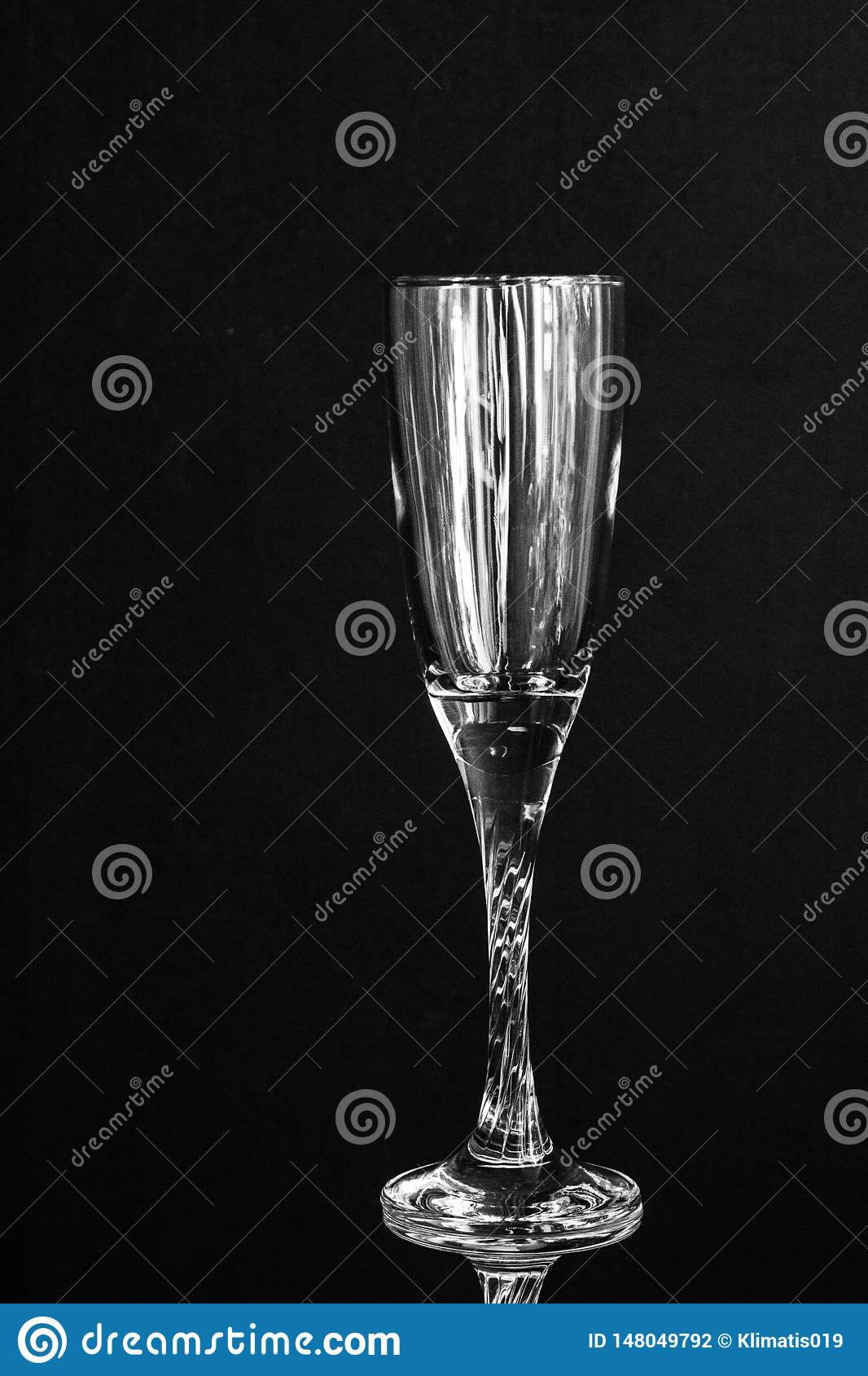 Transparent champagne glass empty on black background.