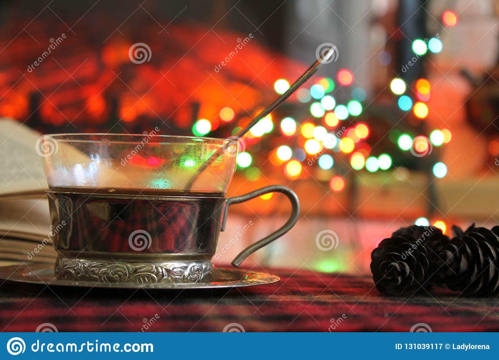 Transparent Cup of tea in a steel Cup holder on the background of a burning fireplace and Christmas garland