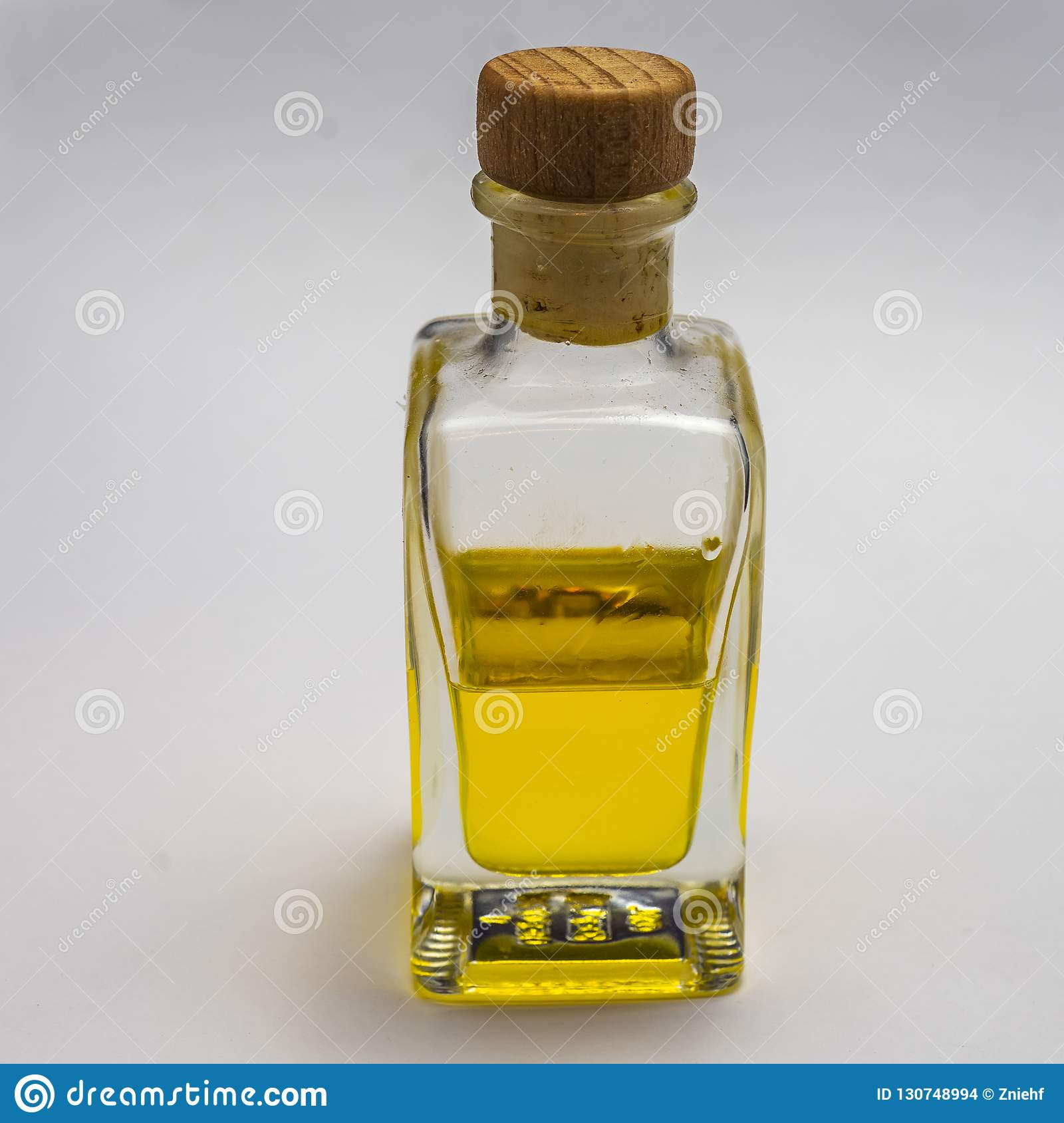 Transparent rectangular glass bottle with a cork stopper. Half filled with a yellow luminous liquid, exposed against a white backg