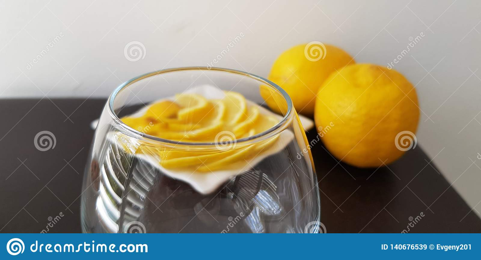 Transparent vine glass on brown table with lemons slices