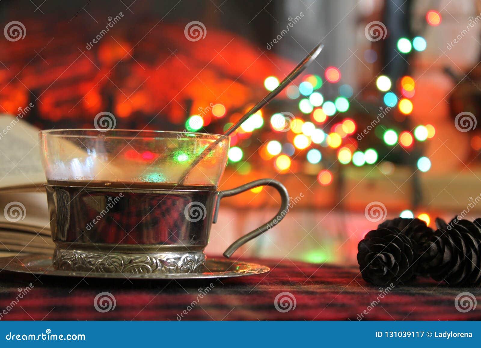 Transparente Tasse Tee in einem Stahlbecherhalter auf dem Hintergrund eines brennenden Kamins und der Weihnachtsgirlande