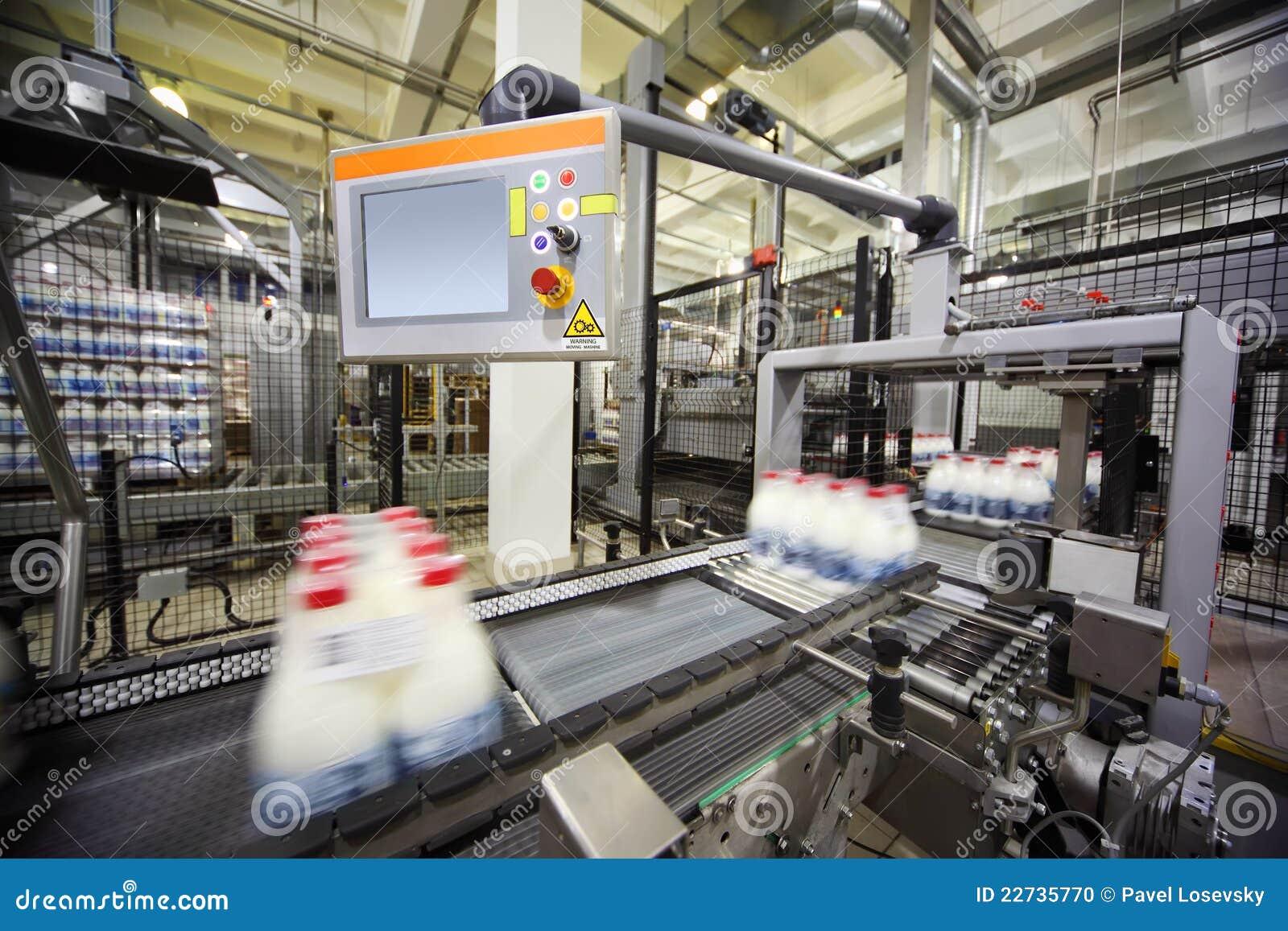 Transportador con las botellas de leche envueltas en la fábrica