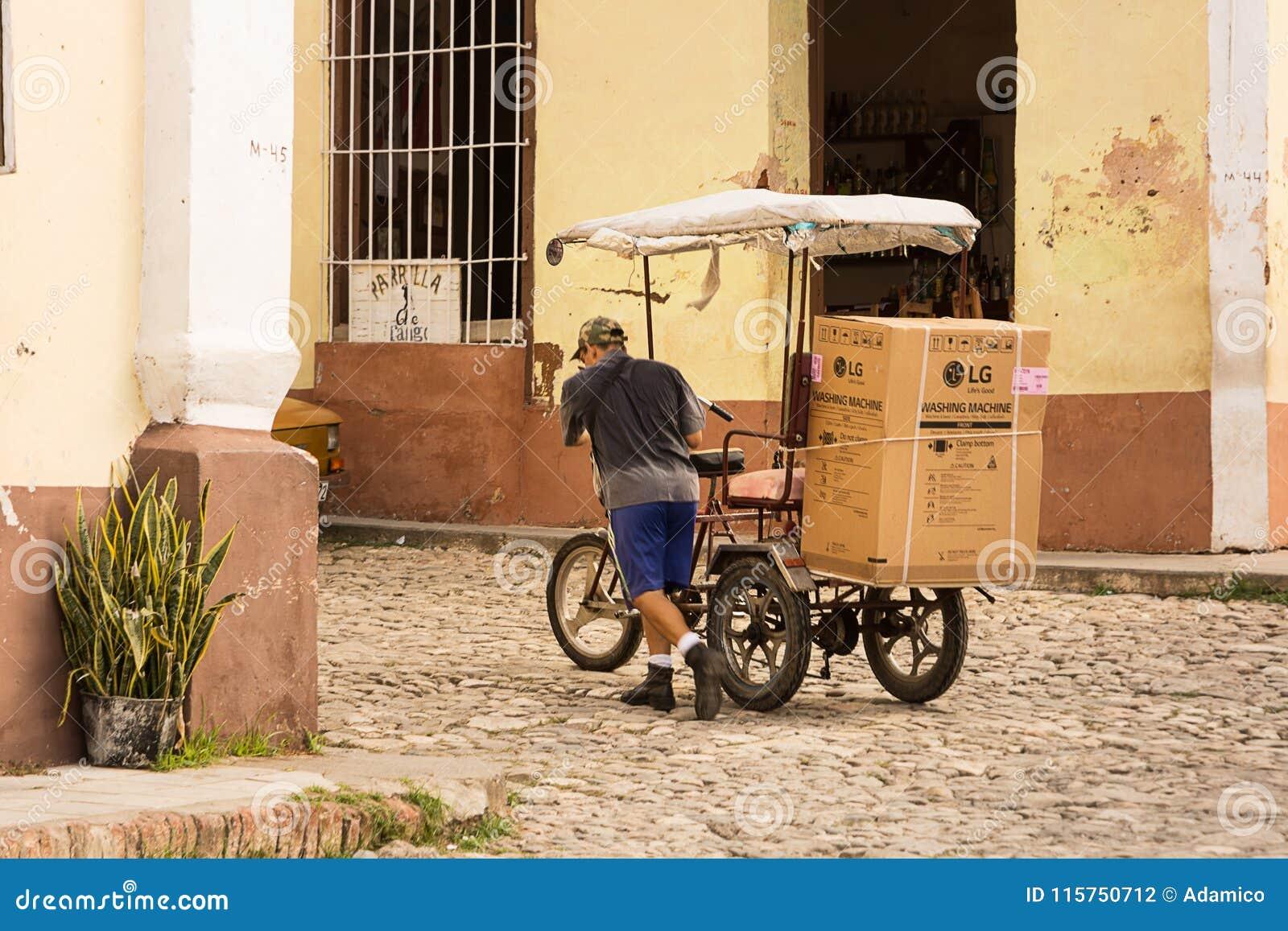 Transporte de una lavadora moderna con una bicicleta en tri
