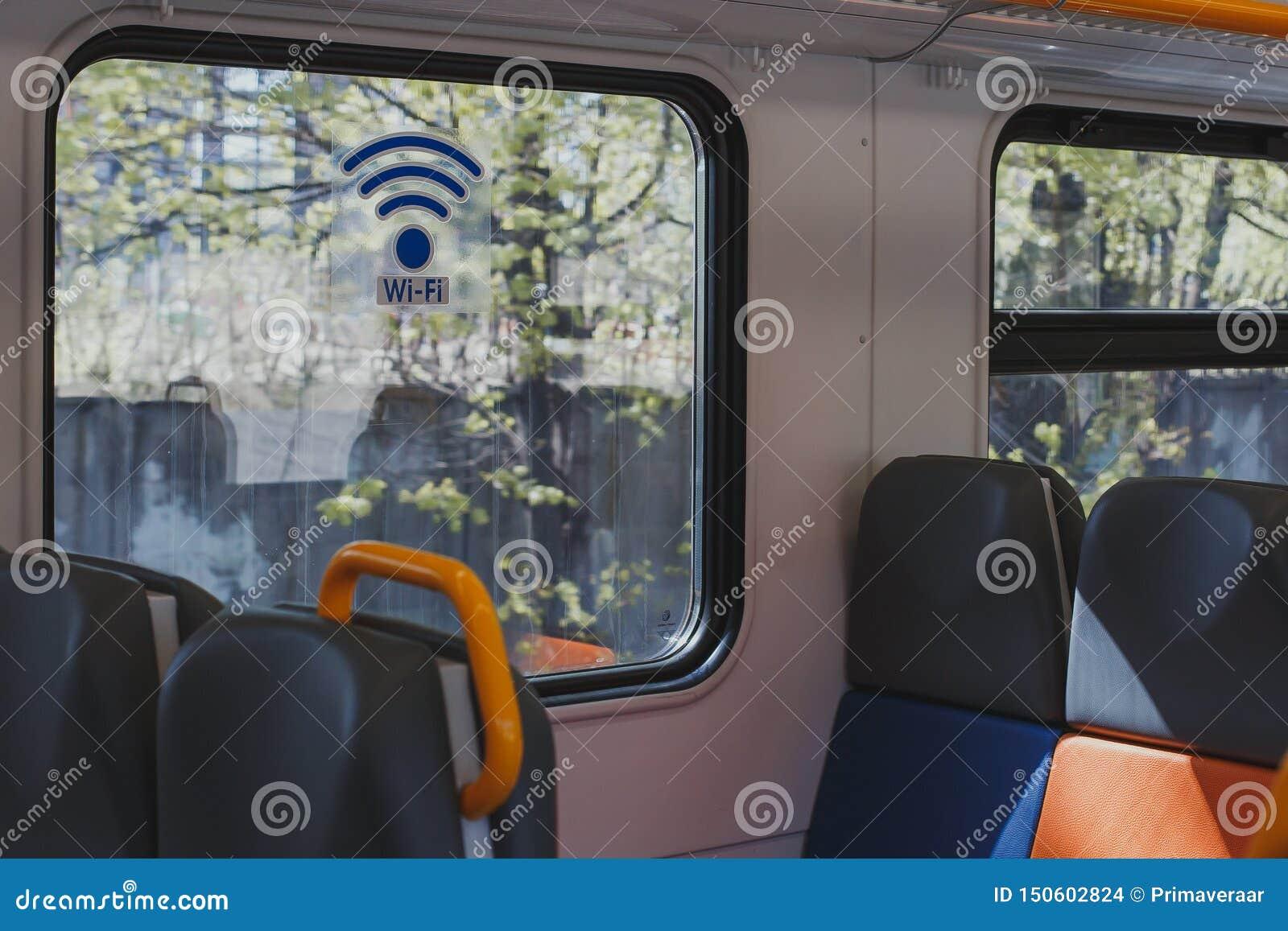 Transporte vazio do trem com assentos coloridos e uma etiqueta na janela WI-FI