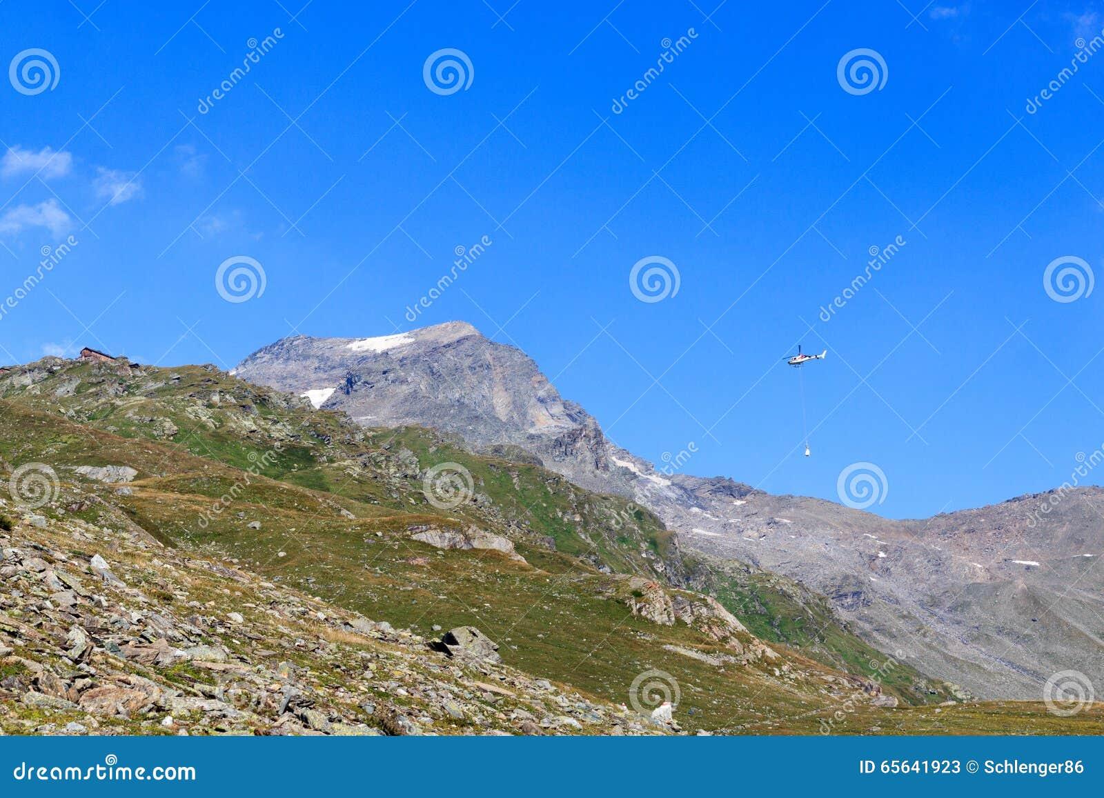 Transportez le vol d hélicoptère avec des approvisionnements et le panorama de montagne avec la hutte alpine, Alpes de Hohe Tauer