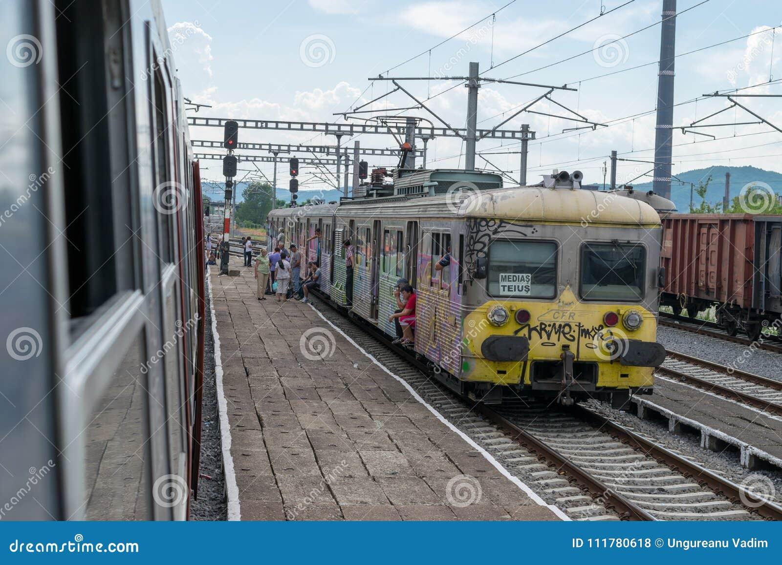 TRANSYLVANIA REGION, ROMANIA - 1 JULY 2016: People waiting for the train to go on in rural Transylvania, Romania.