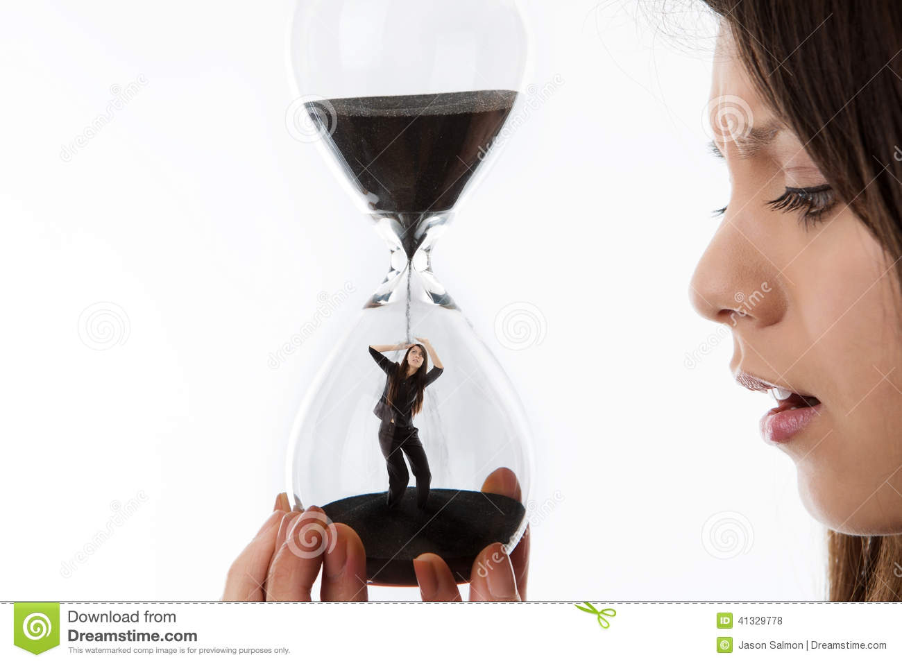 Woman holding up a hour glass sand timer watching time slip away with ...