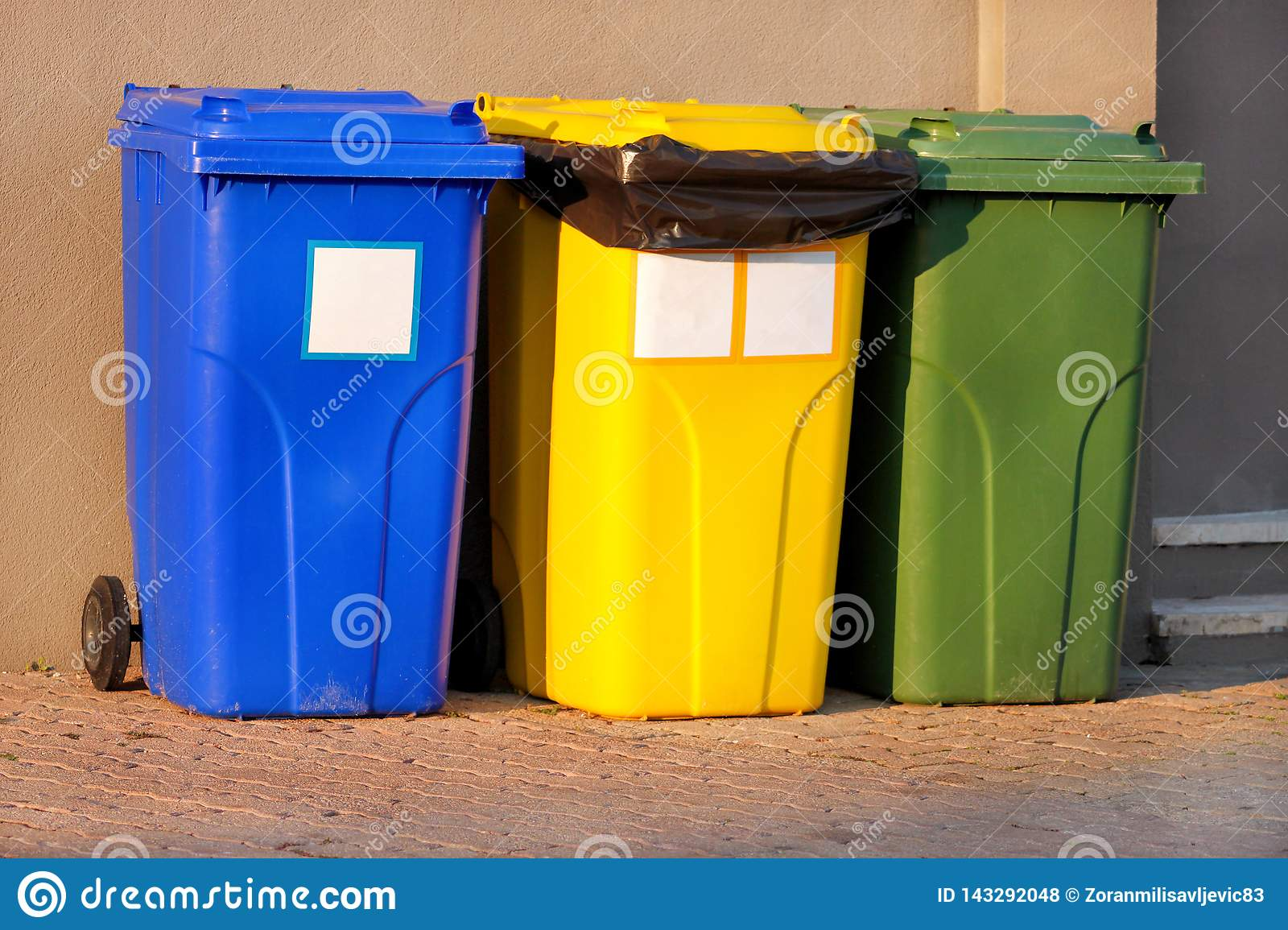Trash can, garbage bin, recycling bin in tourist complex resort, waiting to be picked up by garbage truck. Blue, yellow and green.