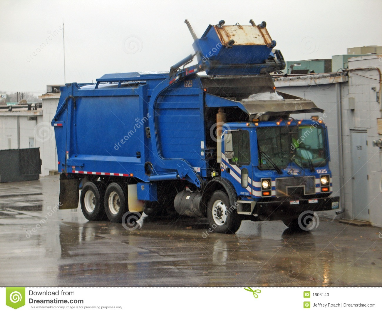 Blue garbage truck collecting trash in the rain.