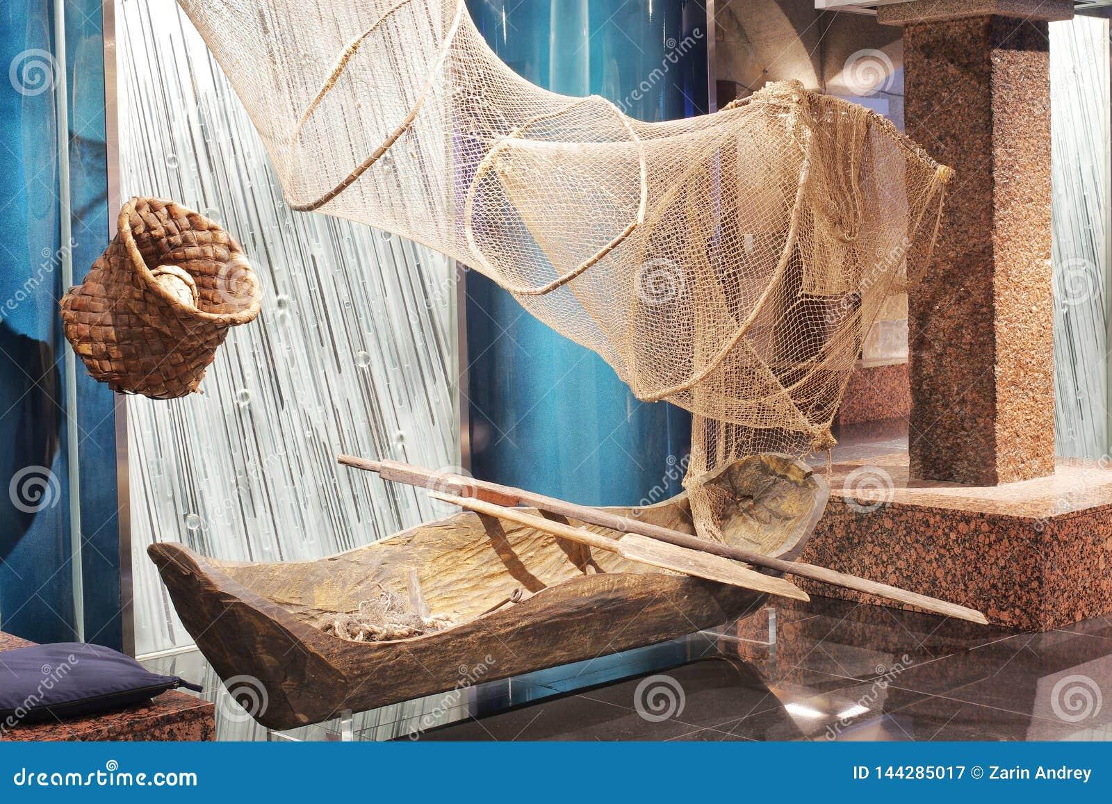 Trastos de un pescador antiguo, de un barco cavado de la madera y de una red para pescar