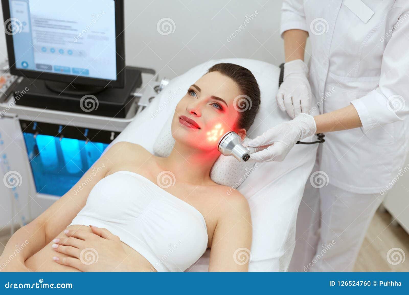 Tratamento claro conduzido vermelho Mulher que faz a terapia facial da pele