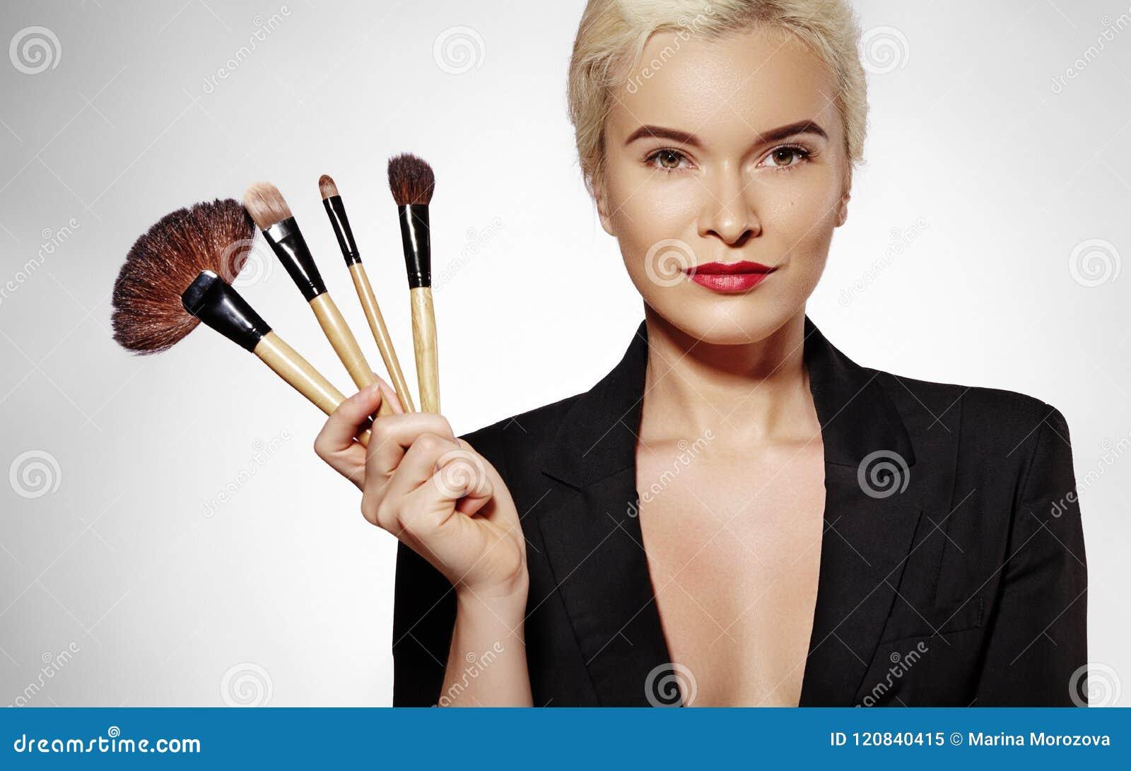 Tratamiento de la belleza Muchacha con los cepillos del maquillaje La moda compensa a la mujer atractiva makeover Artista de maqu