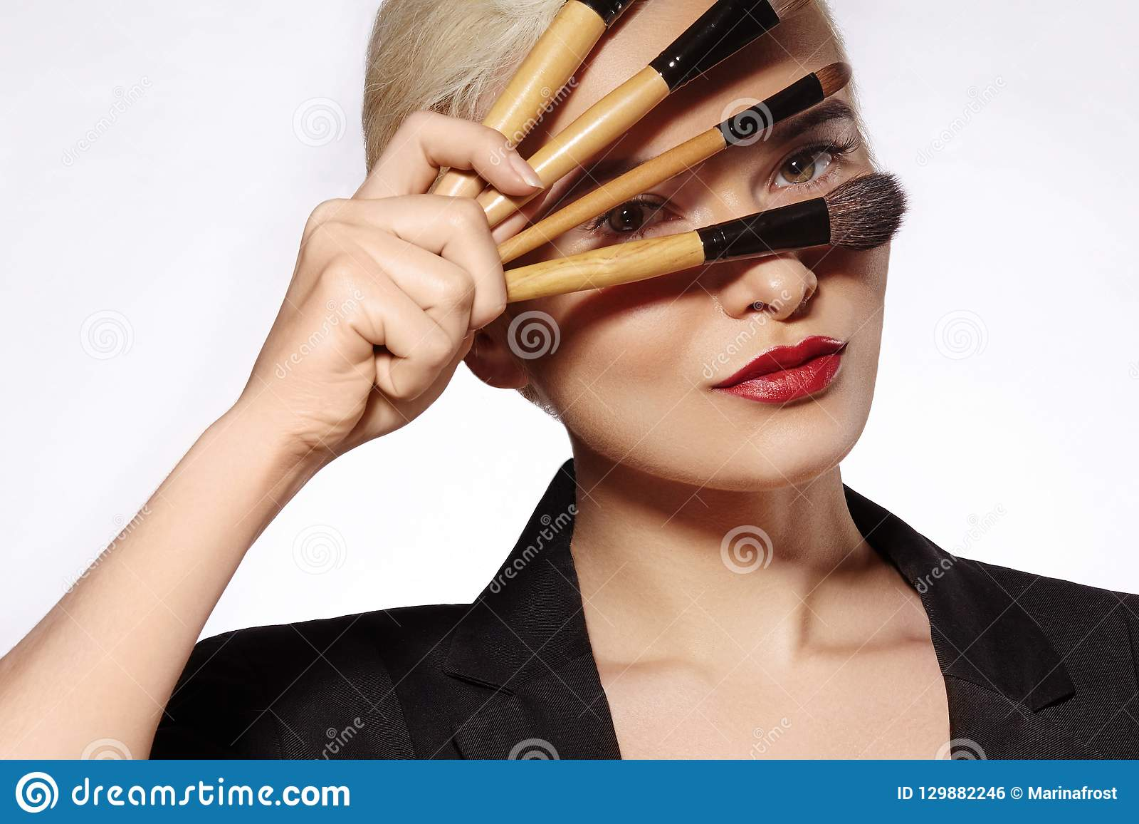 Tratamiento de la belleza Muchacha con los cepillos del maquillaje La moda compensa a la mujer makeover Artista de maquillaje App