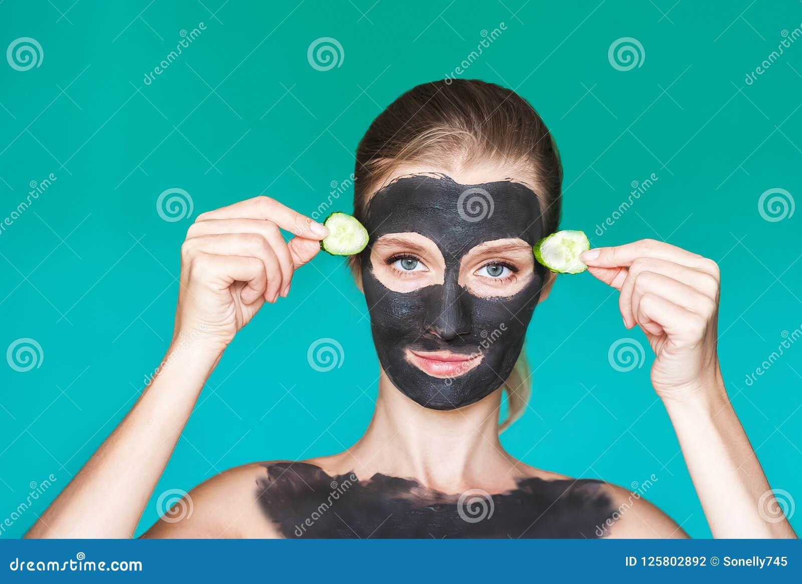 Tratamientos de la belleza Una mujer joven aplica una máscara negra, una crema en su cara con su ascendente cercano de las manos,
