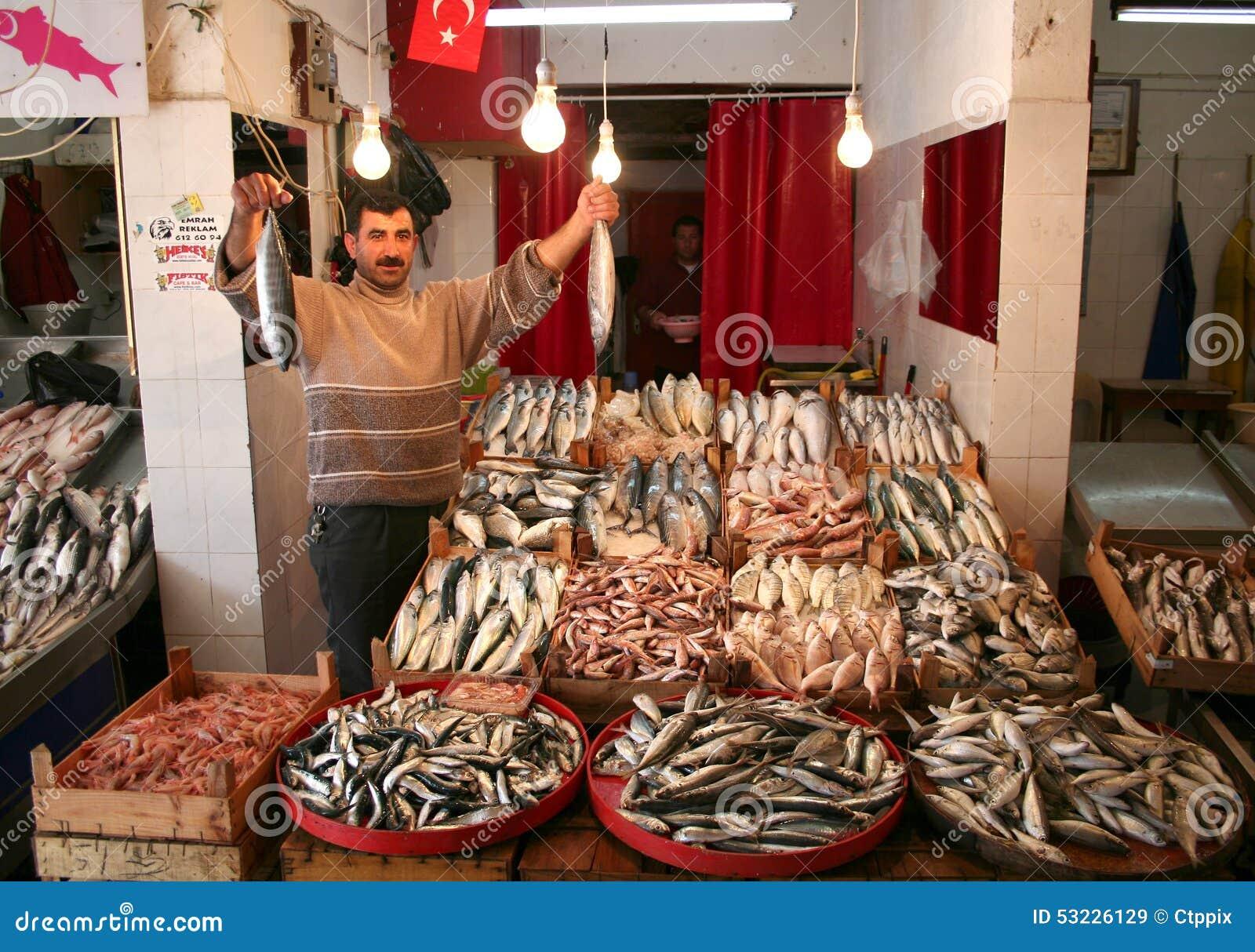 Tratante de pescados que muestra la captura fresca