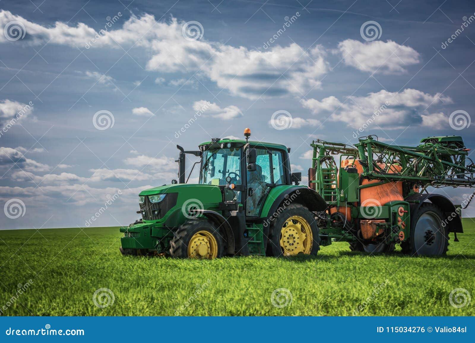 Trator de cultivo que ara e que pulveriza no campo
