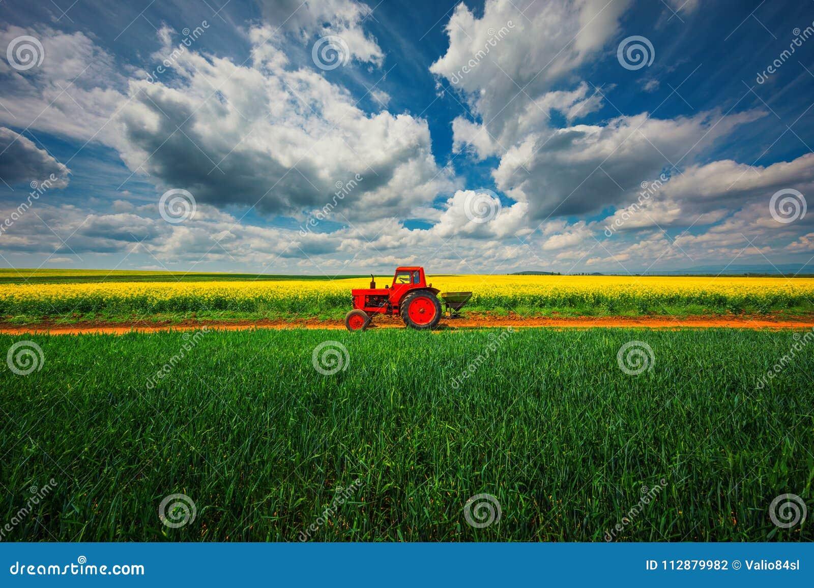 Trator nos campos agrícolas e nas nuvens dramáticas