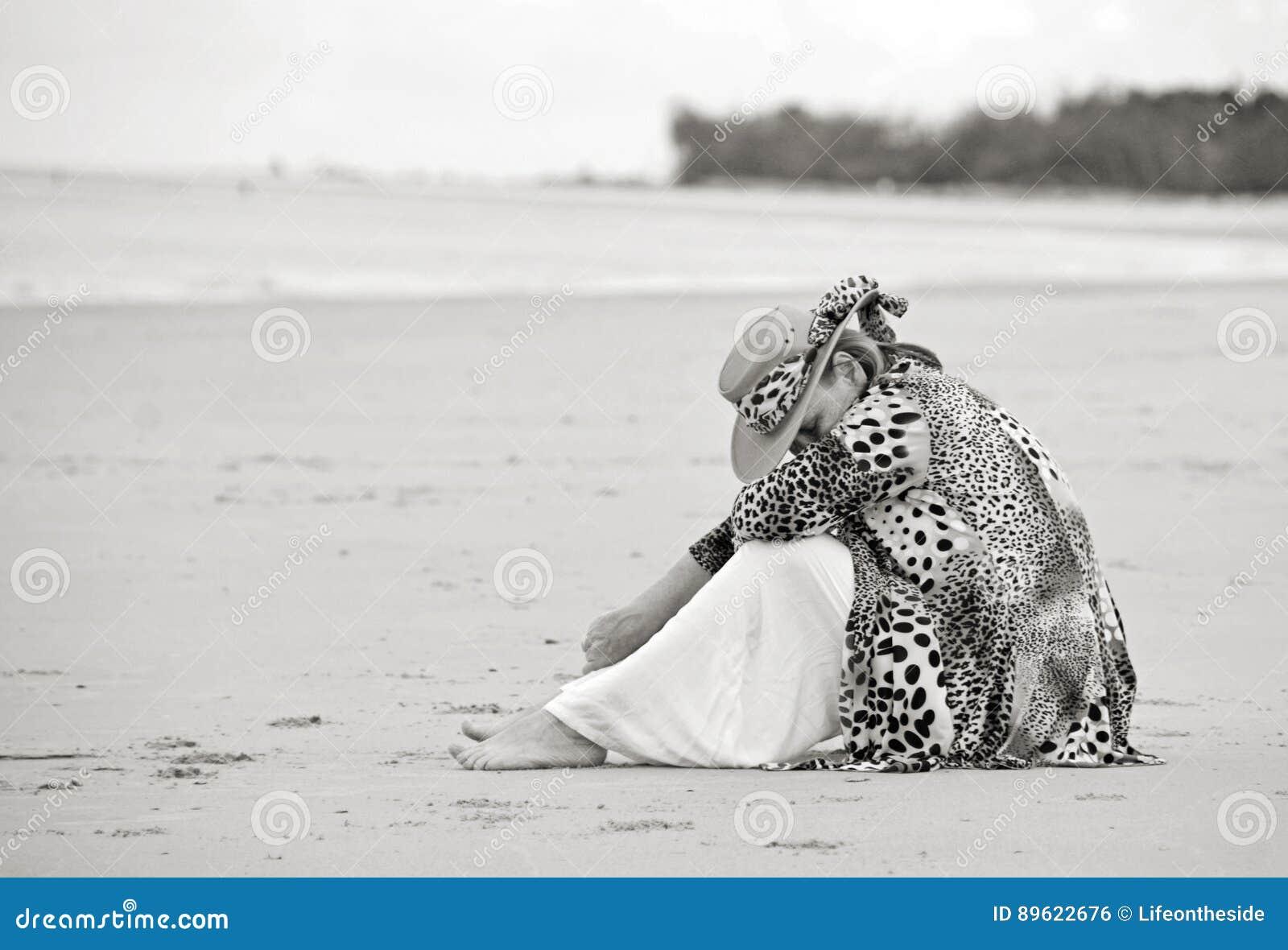 Traurige deprimierte Sorgen machende Frau, die allein auf leerem Strand sitzt