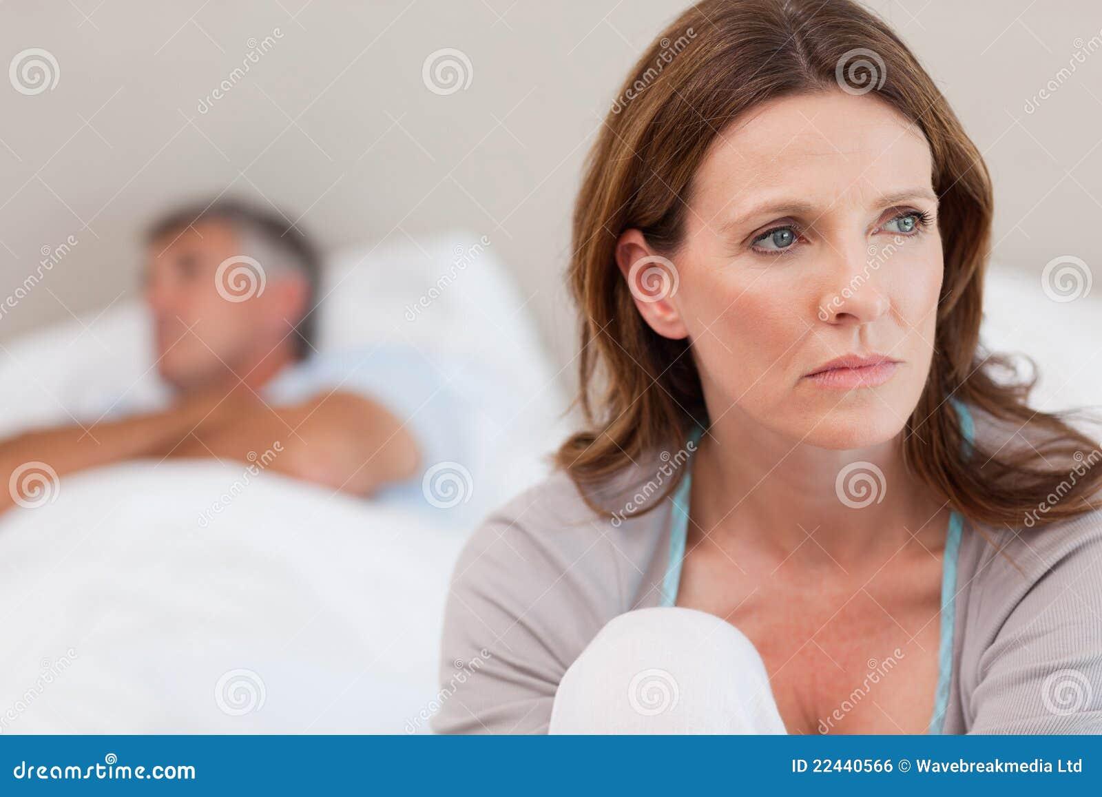 Traurige Frau auf Bett mit ihrem Ehemann im Hintergrund