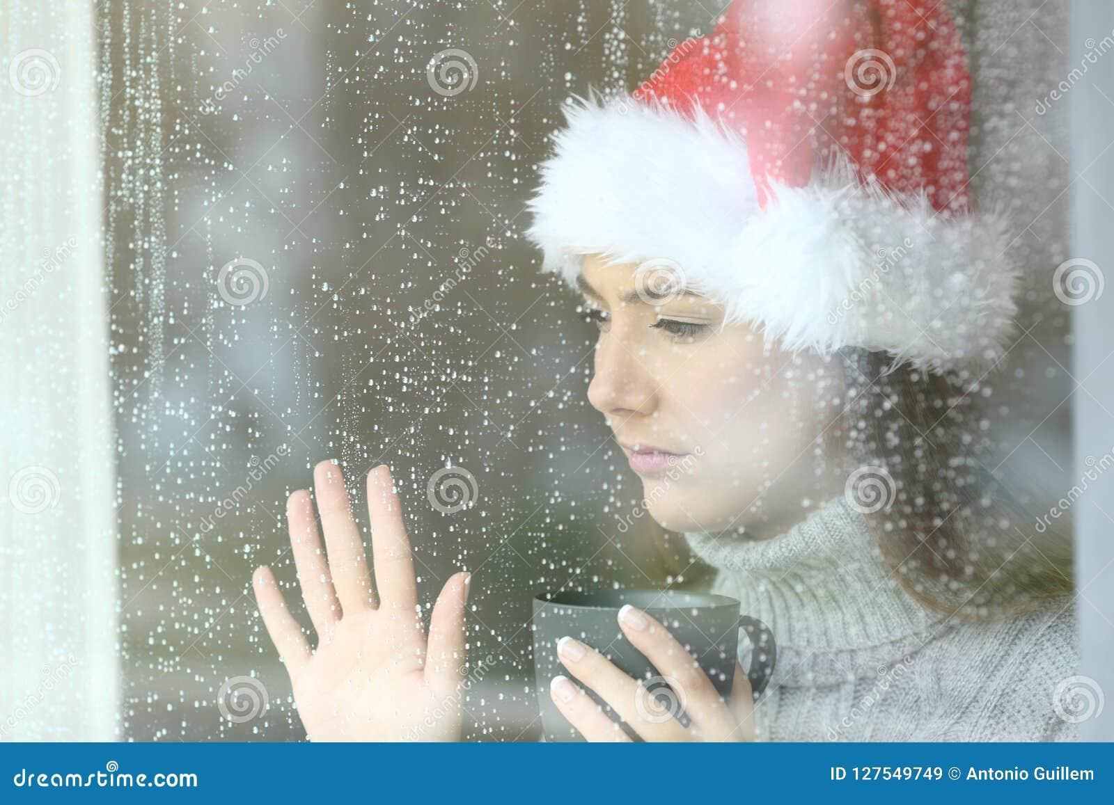 Traurige Frau, die durch ein Fenster im Weihnachten schaut