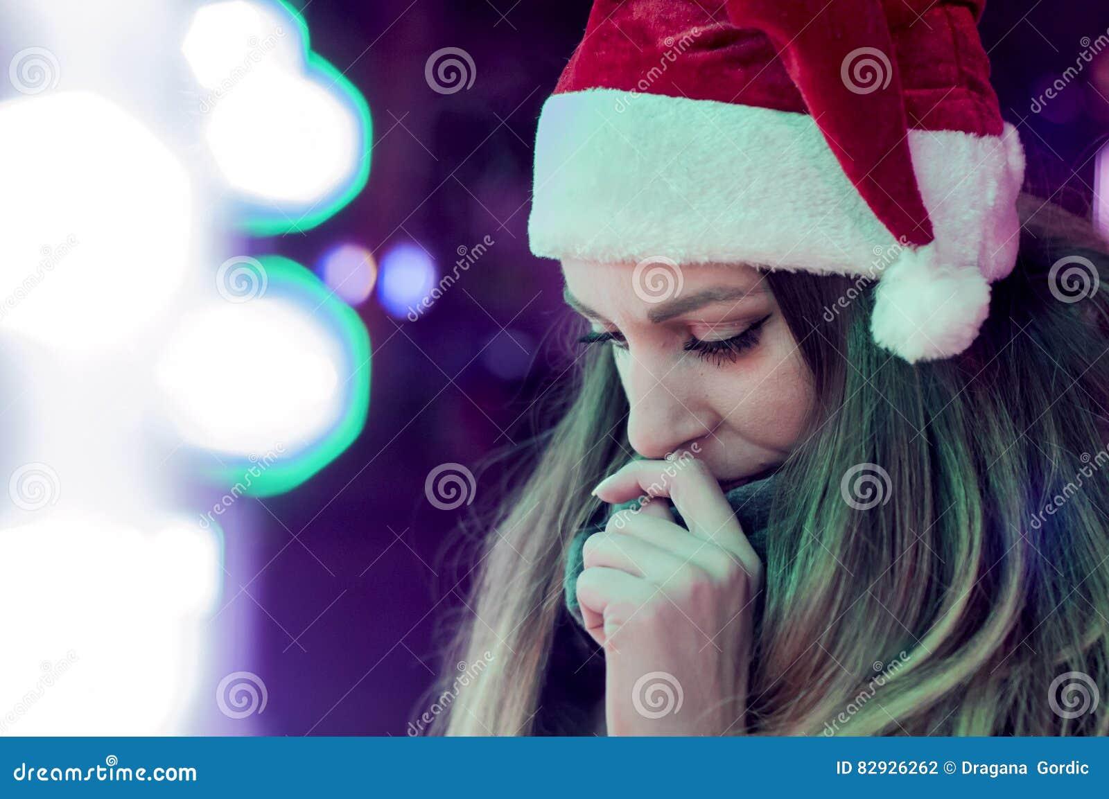 Traurige Frau durch das Weihnachtsbaumnachsinnen über Einsames Weihnachten