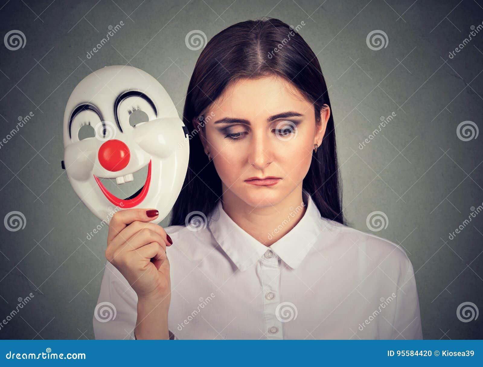 Traurige Frau, welche die Clownmaske ausdrückt Glück entfernt