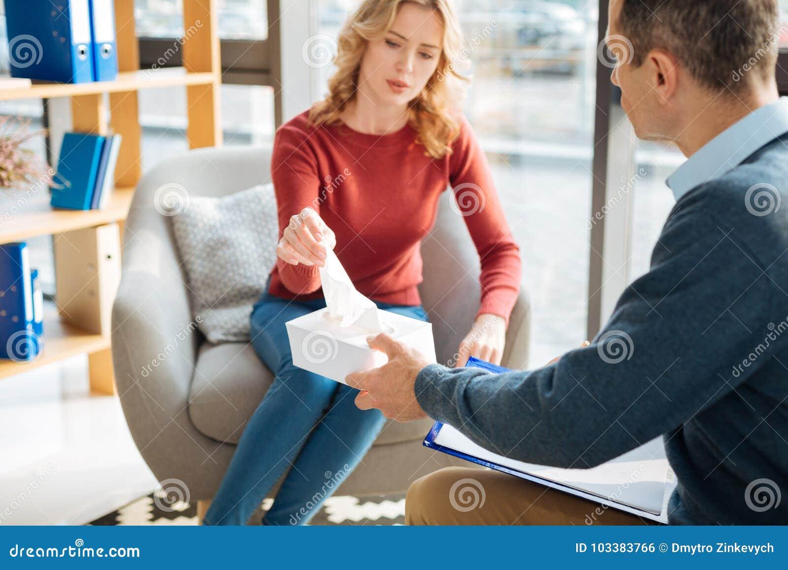 Traurige freudlose Frau, die ein Papiergewebe nimmt