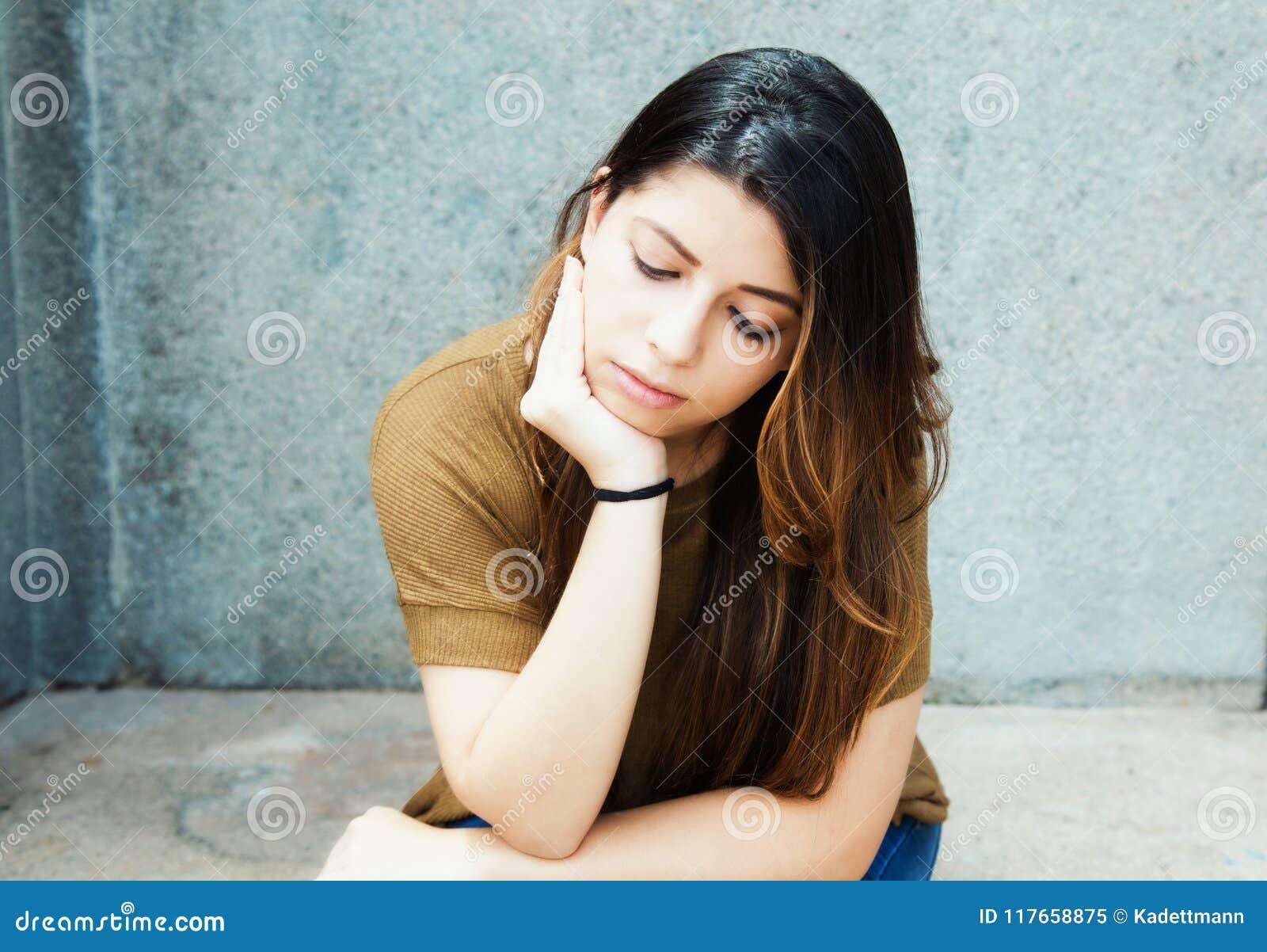 Traurige lateinamerikanische junge erwachsene Frau