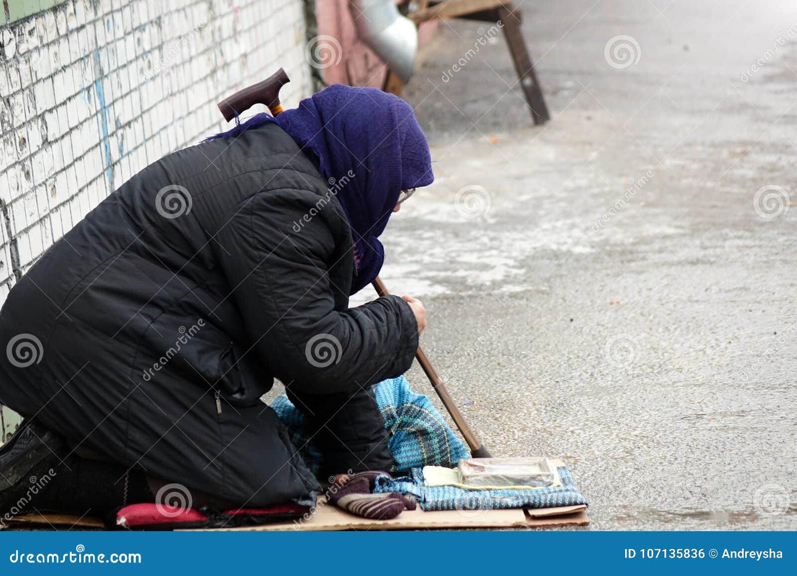 Traurige obdachlose Frau, die auf der Obdachlosen vorbei überschreitet sitzt
