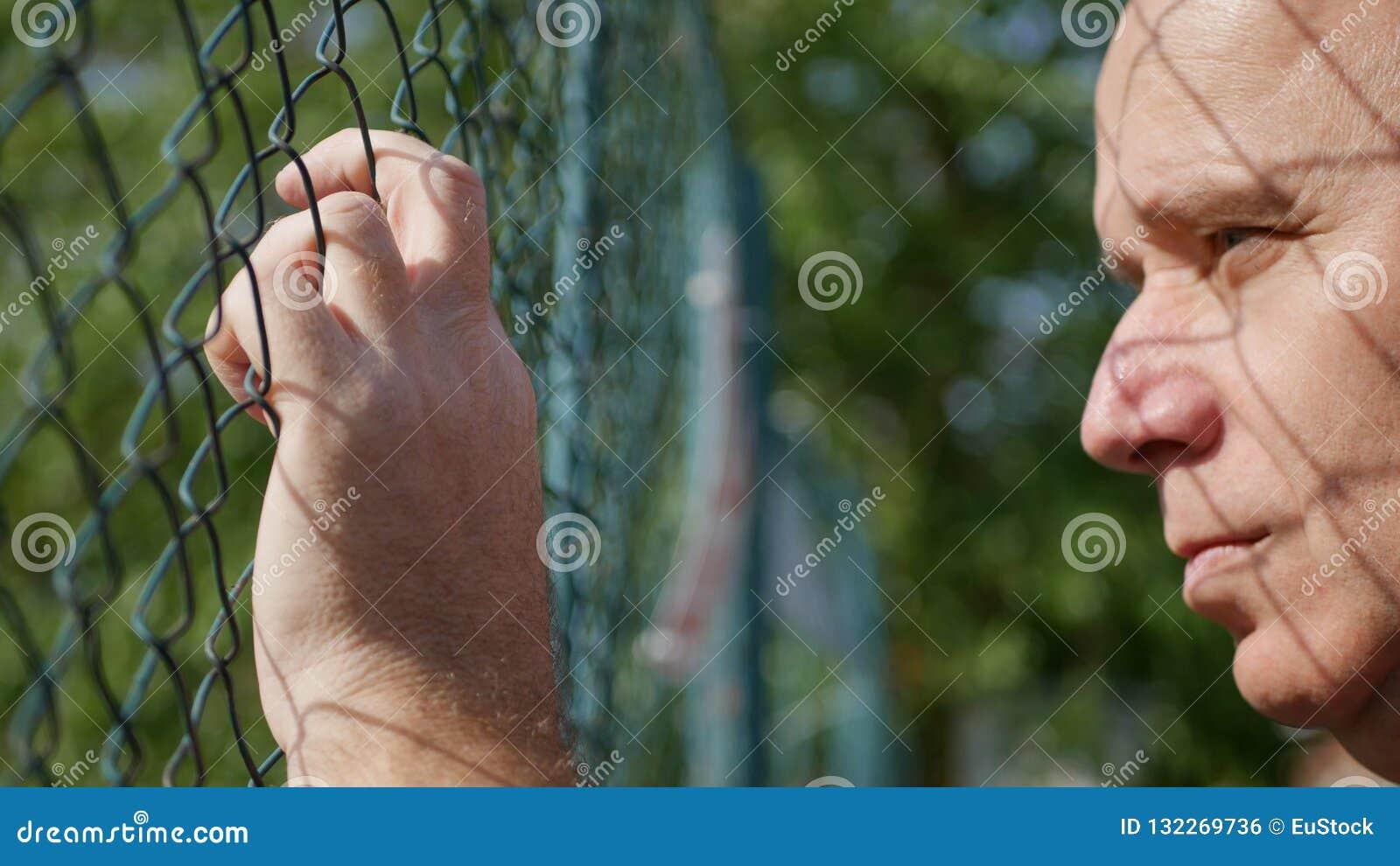 Traurige und Umkippen-Person, die von hinten einen metallischen Zaun schaut